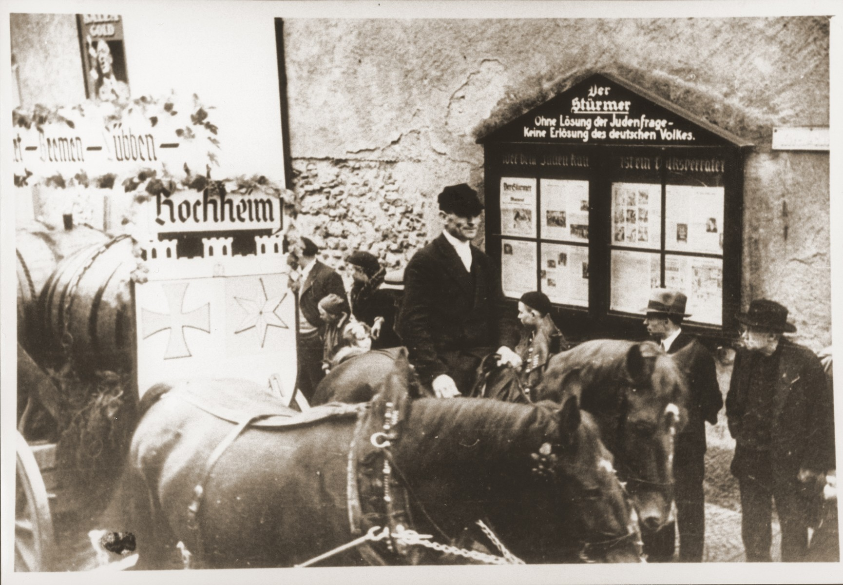 """A decorated beer wagon, one of the floats in the Hochheim parade, proceeds down the Kirchstrasse past a Der Stuermer display box bearing the slogan, """"Without a solution to the Jewish question, there is no salvation for the German people."""""""
