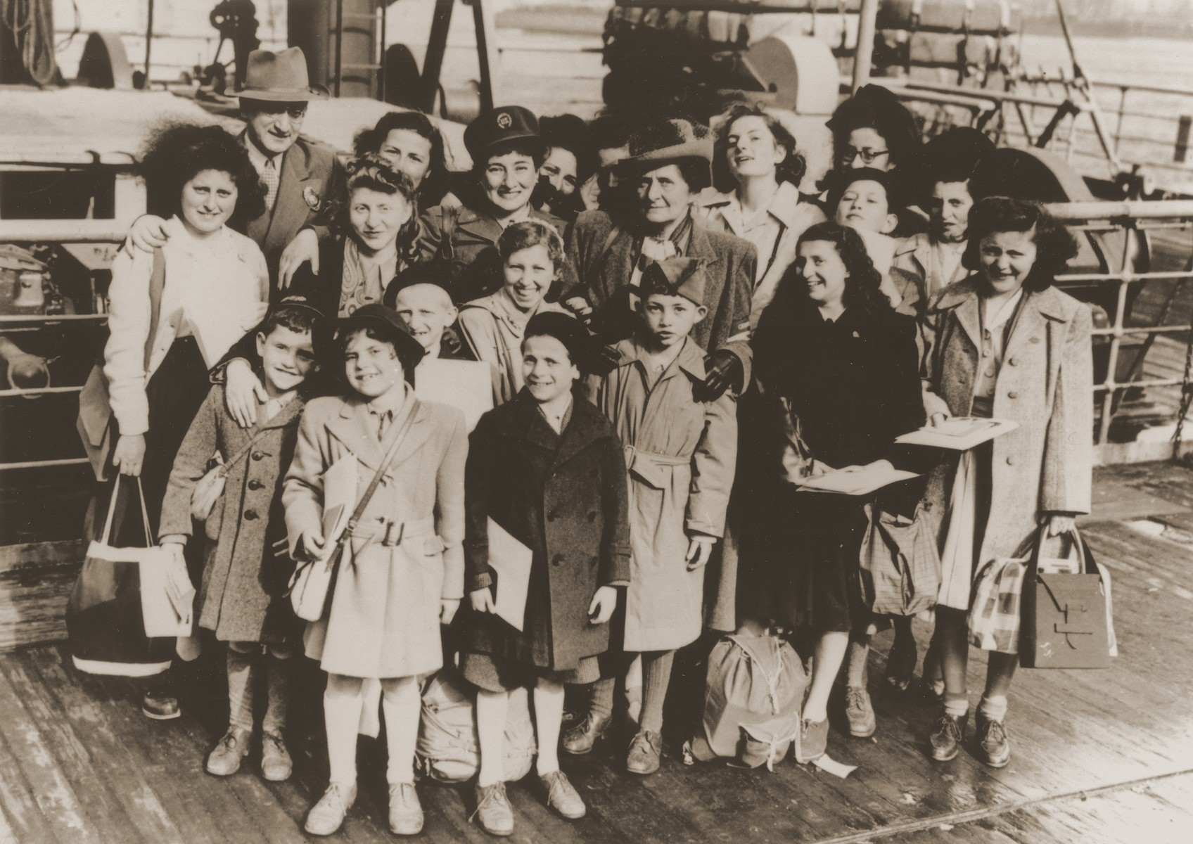 Photo journalist Ruth Gruber (center with cap) poses with a group of Jewish DPs who have just arrived from Europe.  Also pictured are Anneliese Kohn (back row, face partially obscured); siblings Sima (second row, second from right), David and Asher (front row, third from left) Halberstam; siblings Leo and Berthe Dreyfuss (front row, first and second from left).