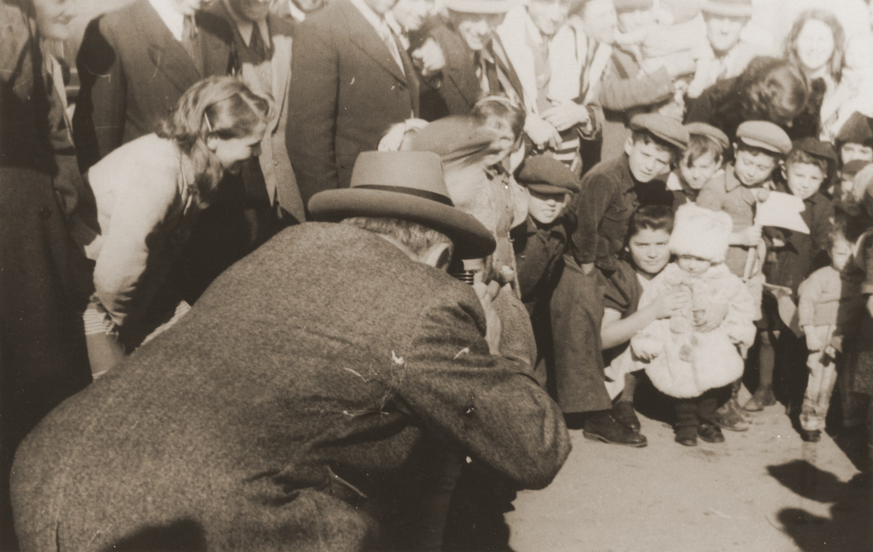 Rabbi Philip Bernstein, adviser on Jewish affairs to the U.S. Army commander in Europe, photographs a group of children in an unidentified DP camp.