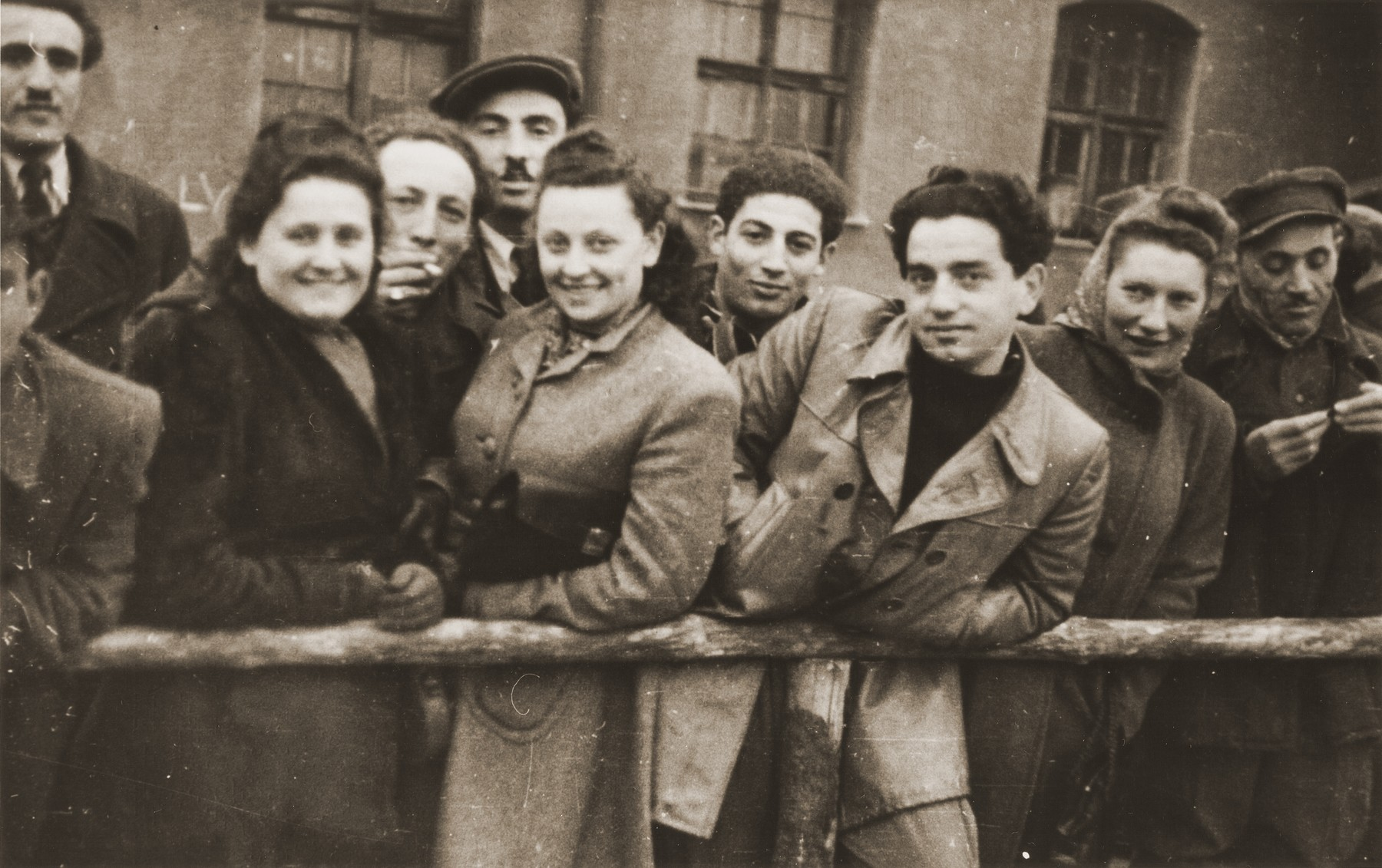 A group of DPs are gathered in front of a barracks in the Landsberg displaced persons camp.