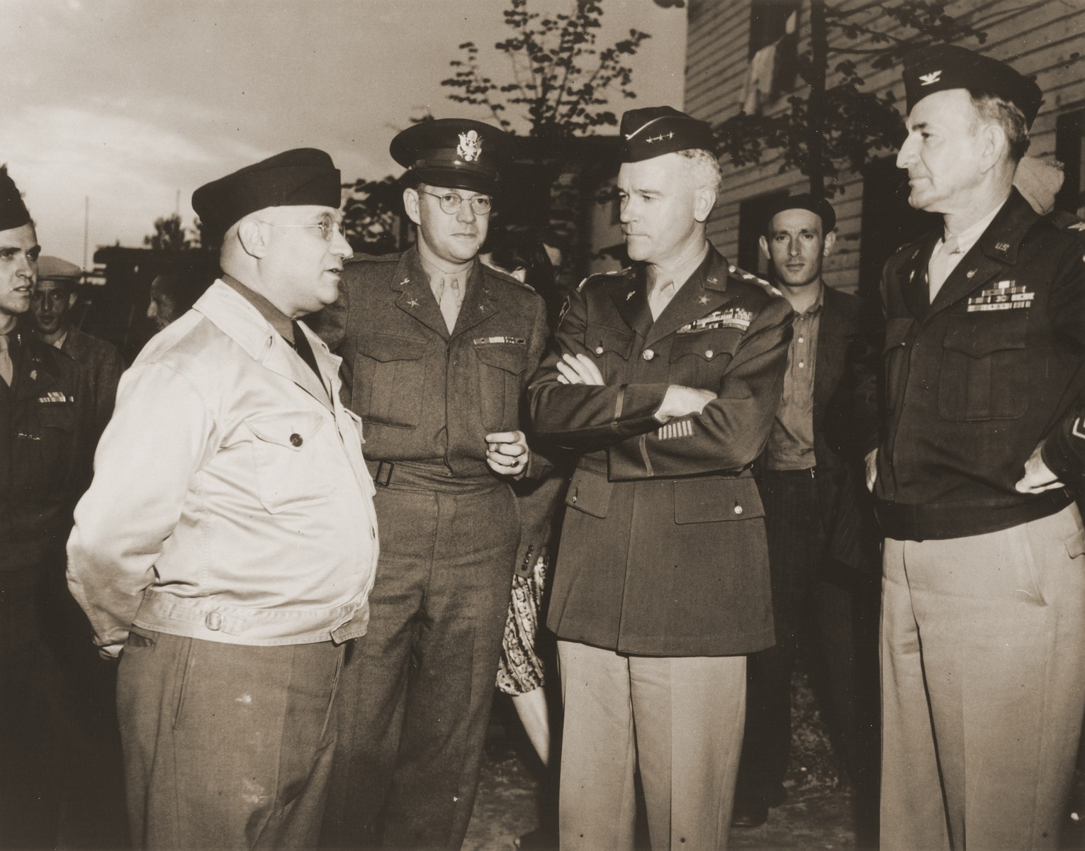 Harold Fishbein, director of the Schlachtensee displaced persons camp, converses with Lt. General Lawton Collins during an official tour the DP camp.  Pictured from left to right are Rabbi Mayer Abramowitz, Harold Fishbein, unknown, Lt. General Lawton Collins, and an aide to the general.