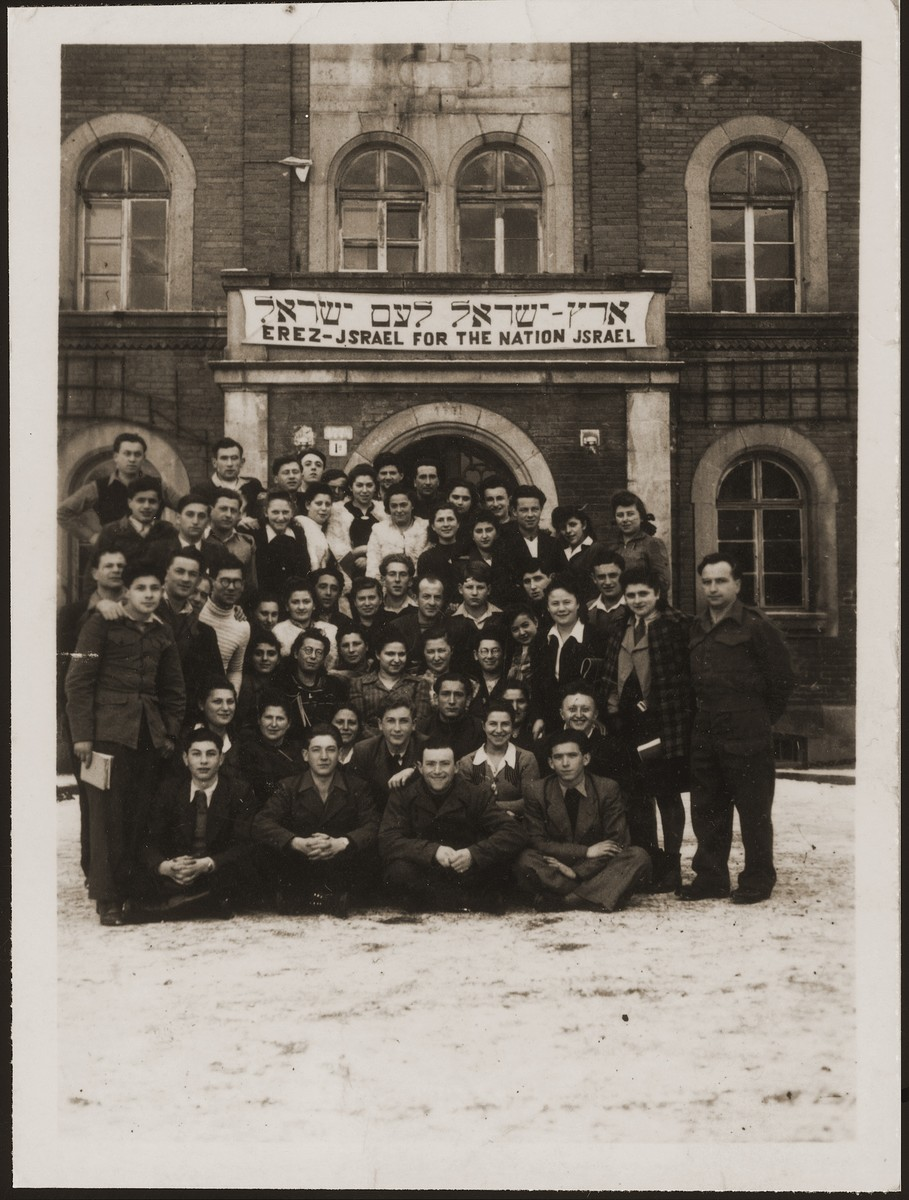 "A group of Jewish DPs pose in front of a building in the Deggendorf DP camp.   The banner reads in Hebrew and English, Erez Israel for the nation Israel (Land of Israel for the People of Israel).  The group, instructed by members of the Jewish Brigade,  was a small, centrist, slightly left-of-center Zionist movement called Noam (literally ""pleasantness"").  Shortly after the photo was taken members of the group formed an agricultural kibbutz to prepare for their aliyah to Israel.  Pictured in the photo are Hadasa Cudzynowska, Henik and Sala Weingarten."