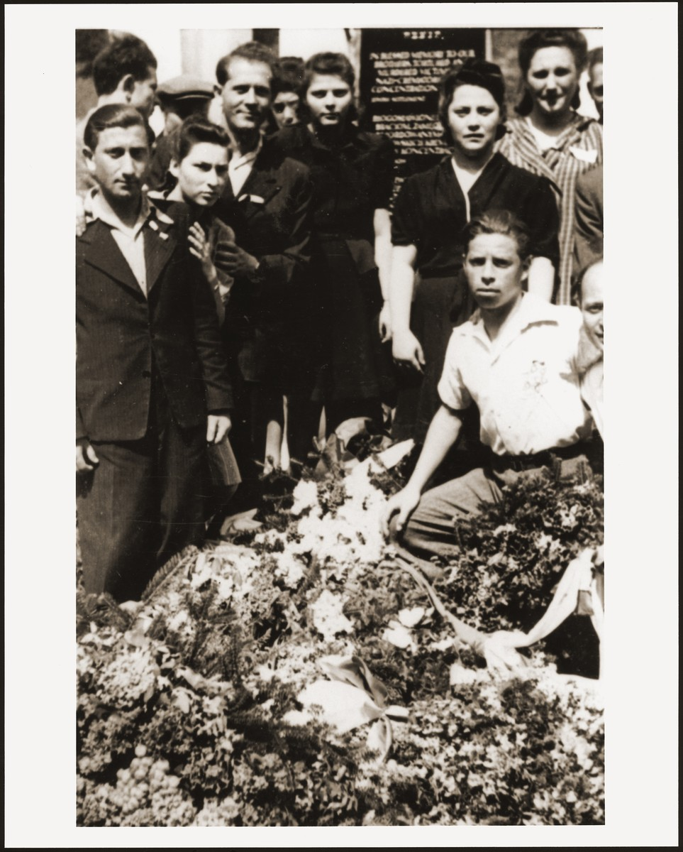 Jewish DPs from the New Palestine displaced persons camp gather around a memorial erected to the Jewish victims of the Nazis.   Among those pictured is Moniek Rozen (far left), Rela Szancer (second from the left), and Kazik Szancer (third from the left).