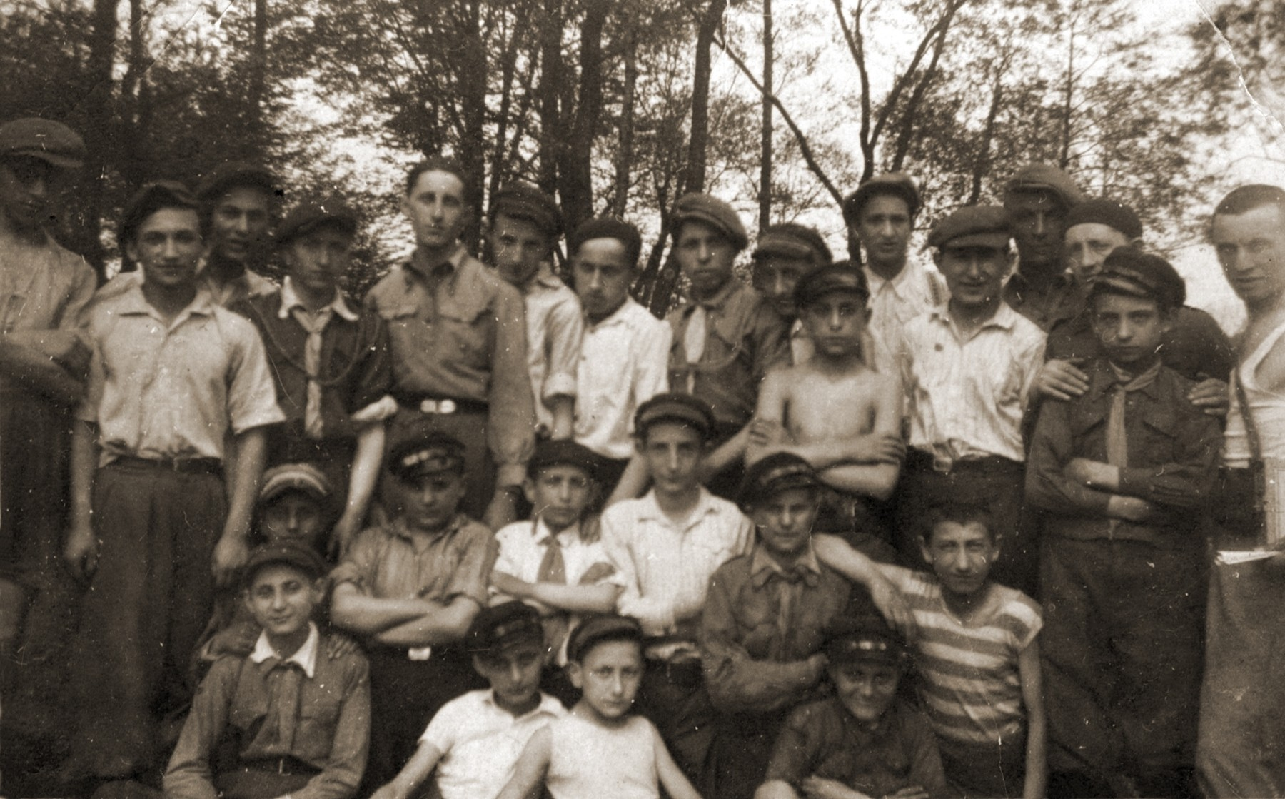 Group portrait of members of the Hashomer Hadati Zionist youth organization on an outing in the woods.  Pictured (top row, from left to right): unknown; Blumenfeld; unknown; Szmuel (Samuel) Gottlieb; Motek Rechnic; Motek Zajac; unknown; Hesiek Rechnic; Motek Ostrowiecki; Ilek Stawski;  Majer Nowomiejski; Szolem Blumenfeld; Mojszele Gruszka; Nordon, and Menachem Bukowski; (second row, left to right) are: Chune Kenner; Icek Rendel; Josek Lenczner; Rueven Lefkowicz; Motek Rendel, and Moniek Rozen (the donor, in striped shirt, aged 13 years);  (front row, from left to right) are: Hercko Lenczner; Jakub Bajtner; Moniek Szeps, and Motek Kenner.