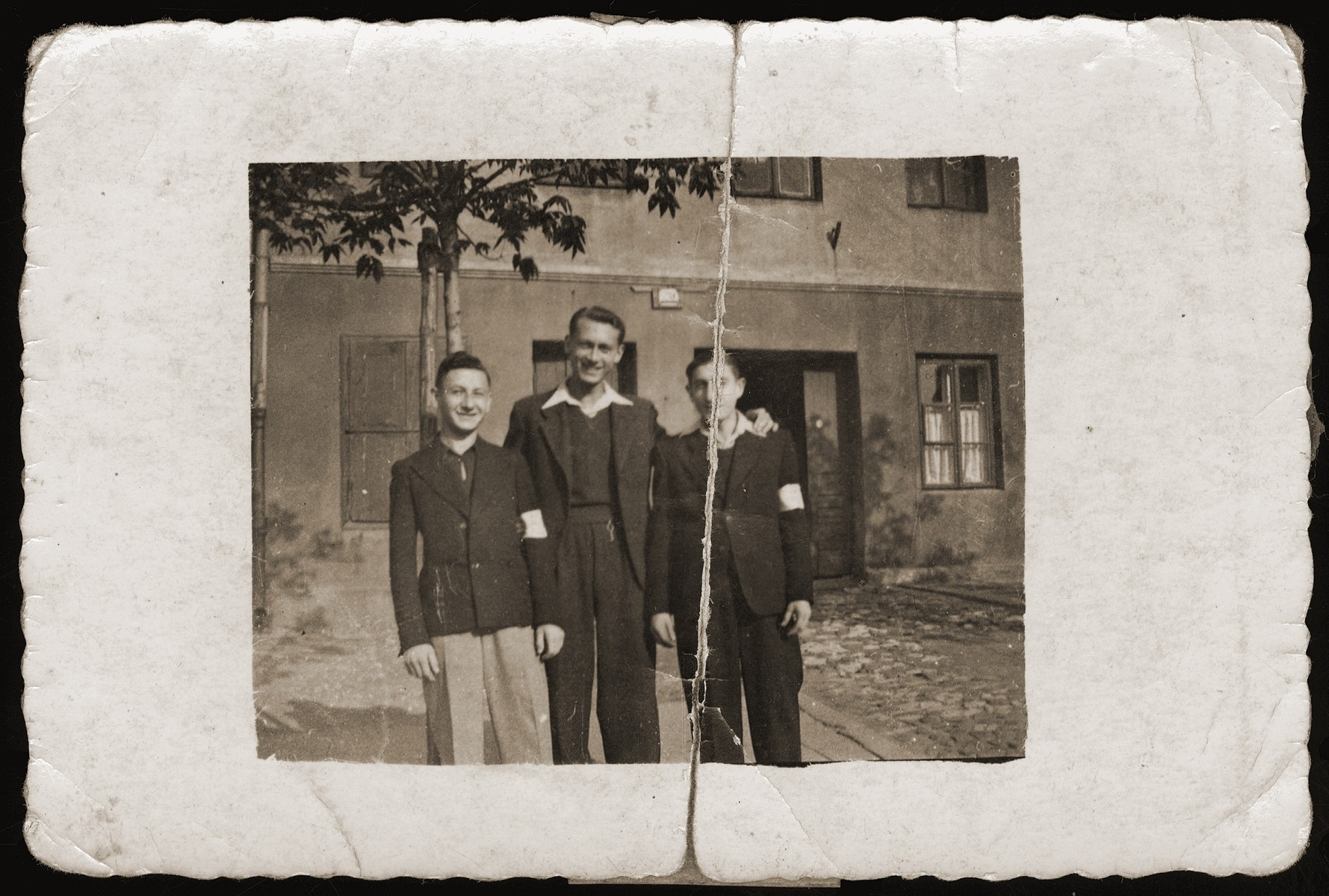 Three Jewish youth pose outside in the Dabrowa Gornicza ghetto.    Pictured from right to left are: Moniek Rozen, Moniek Najfeld and Moniek Szeps.