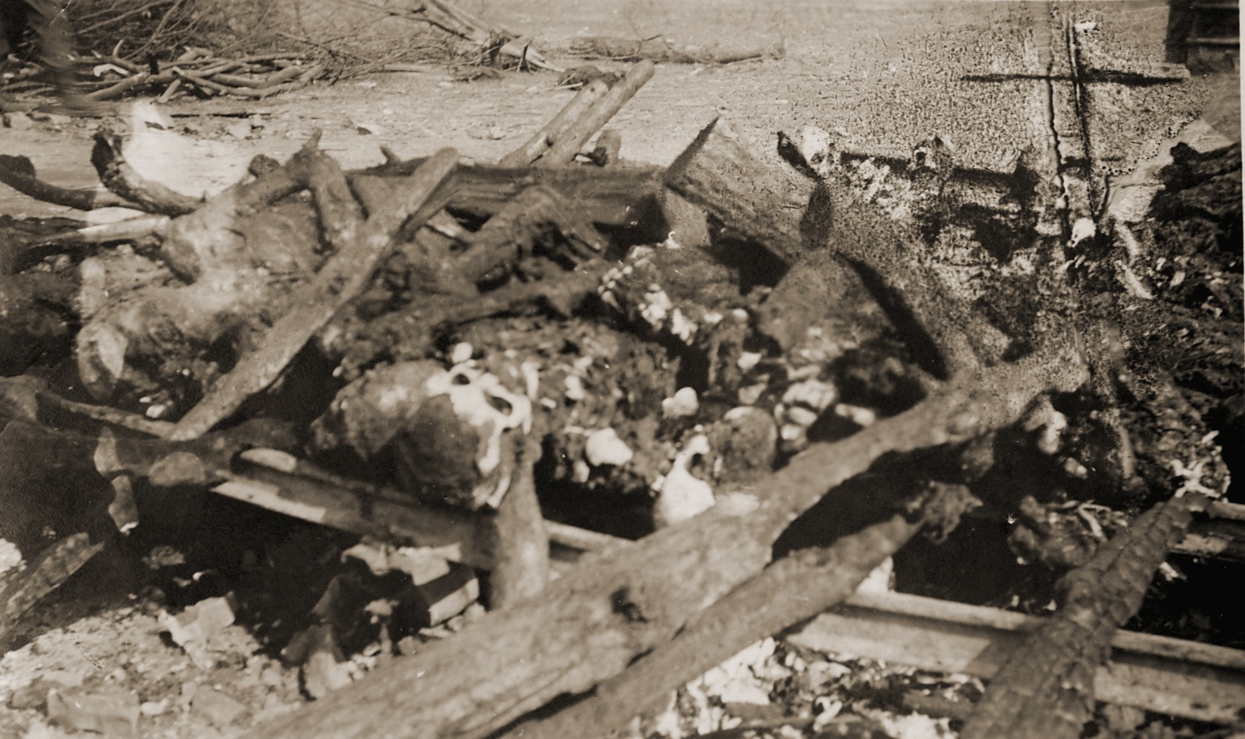 The charred corpses of prisoners burned on a pyre just prior to the liberation of the camp by the American Army.