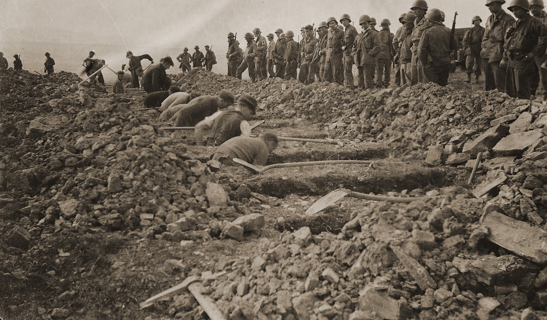 American troops look on as German civilians from nearby towns dig graves for corpses found in the Ohrdruf concentration camp.