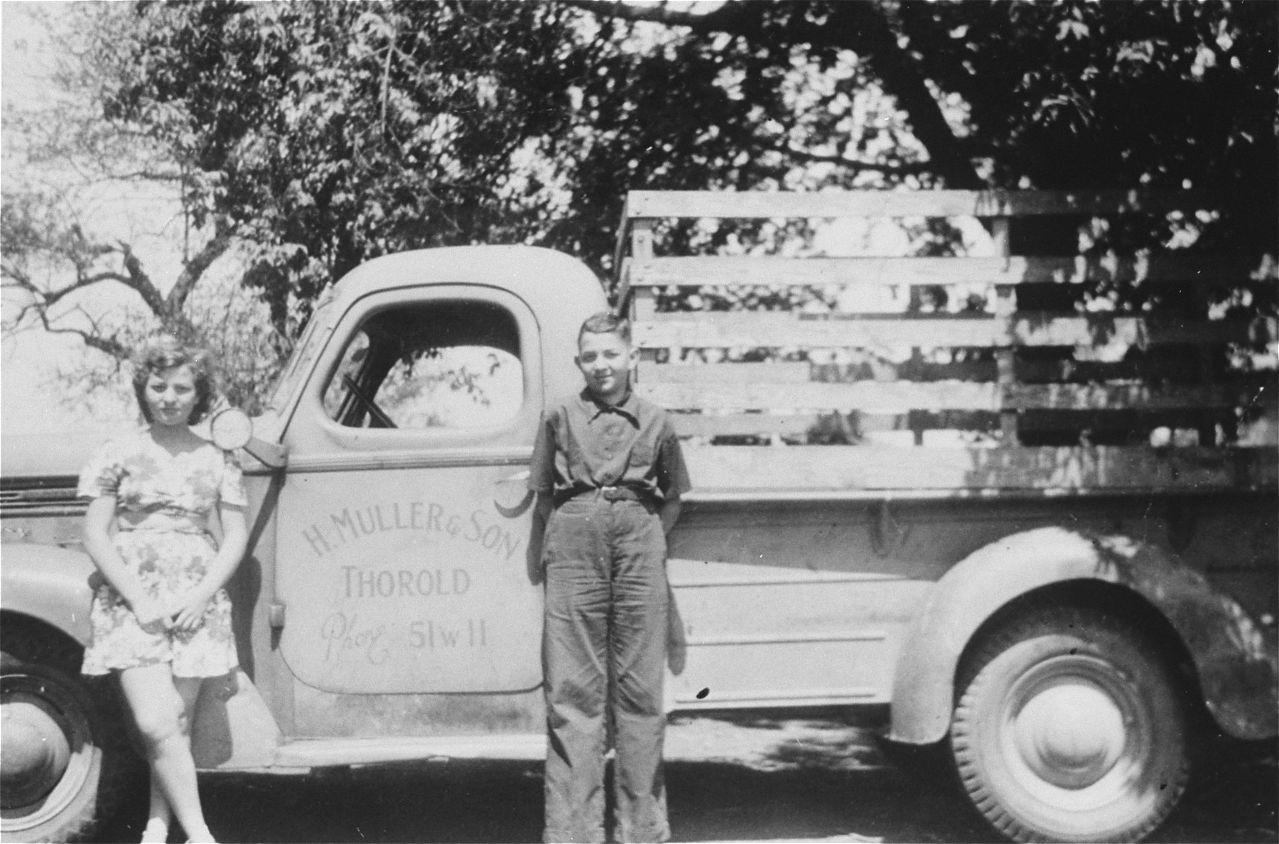 Jewish refugee youth pose in front of their father's farm truck which bears the name of the former family firm in Czechoslovakia.    Pictured are Henry and Alice Muller, the donor's two children.