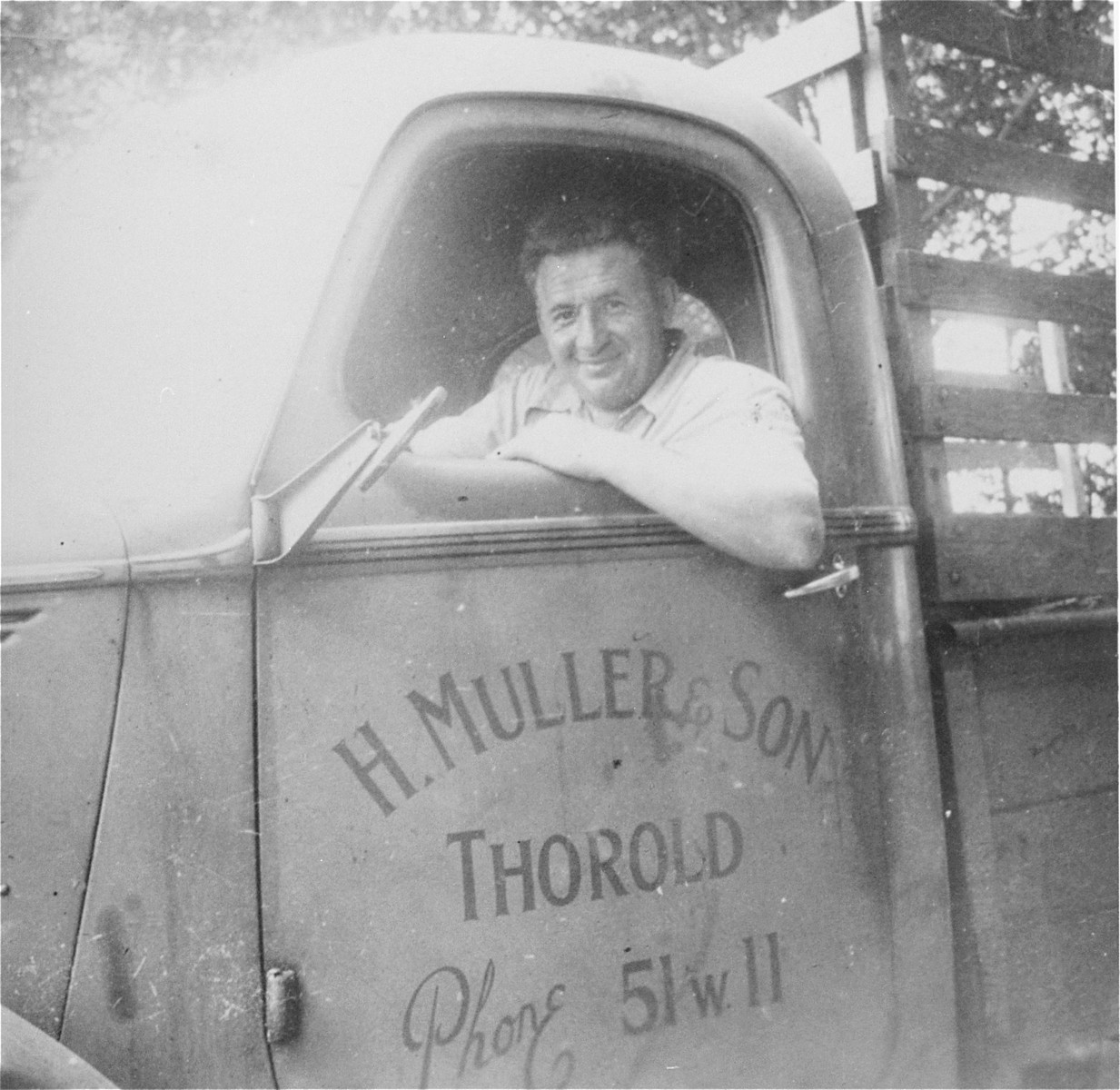 Portrait of Nandor Muller in his truck bearing the same company name as his grandfather's wholesale grain business in Czechoslovakia.