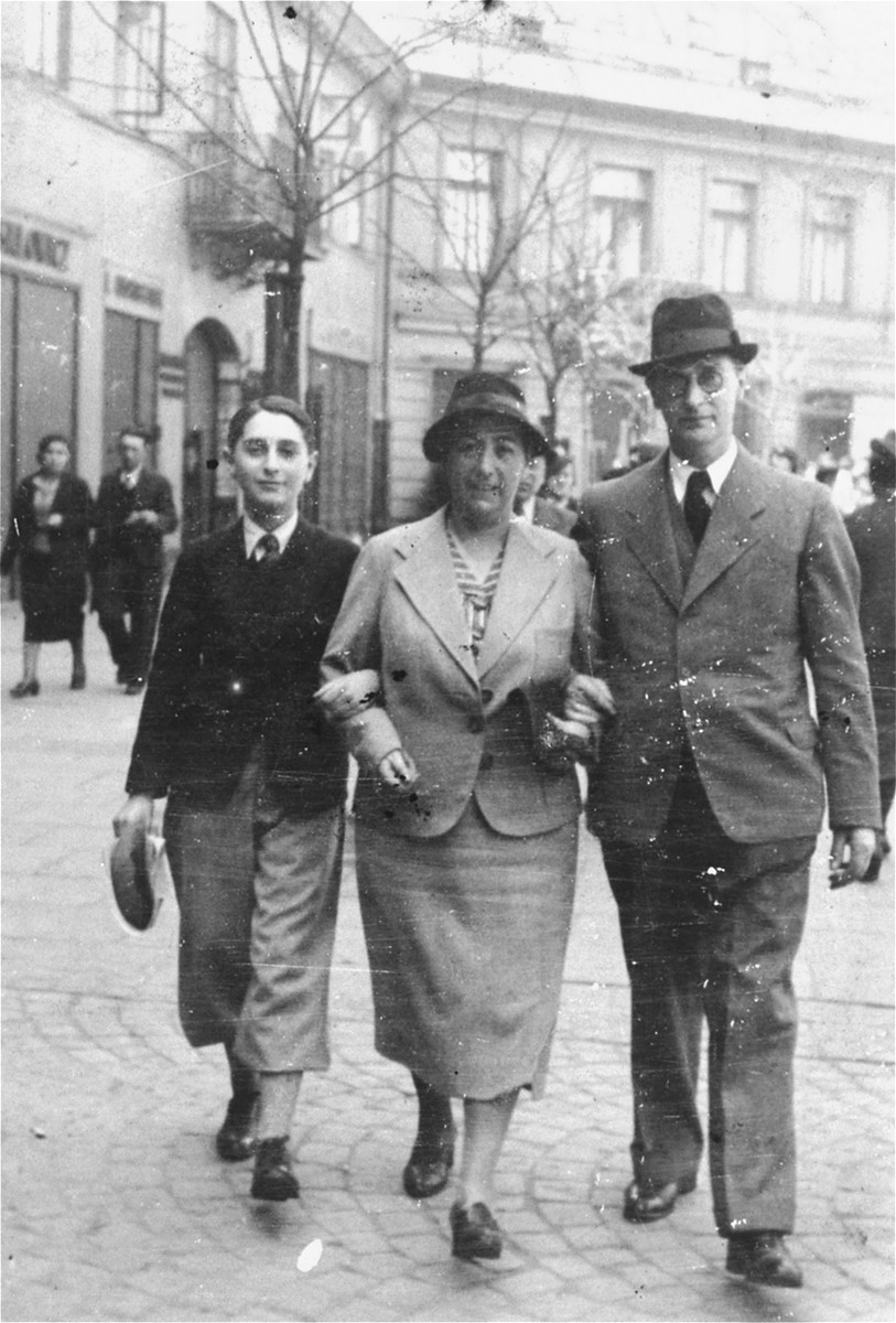 Herman Neudorf and his parents walk along a commercial street in Lodz.    The Neudorfs were expelled from Germany in 1938.