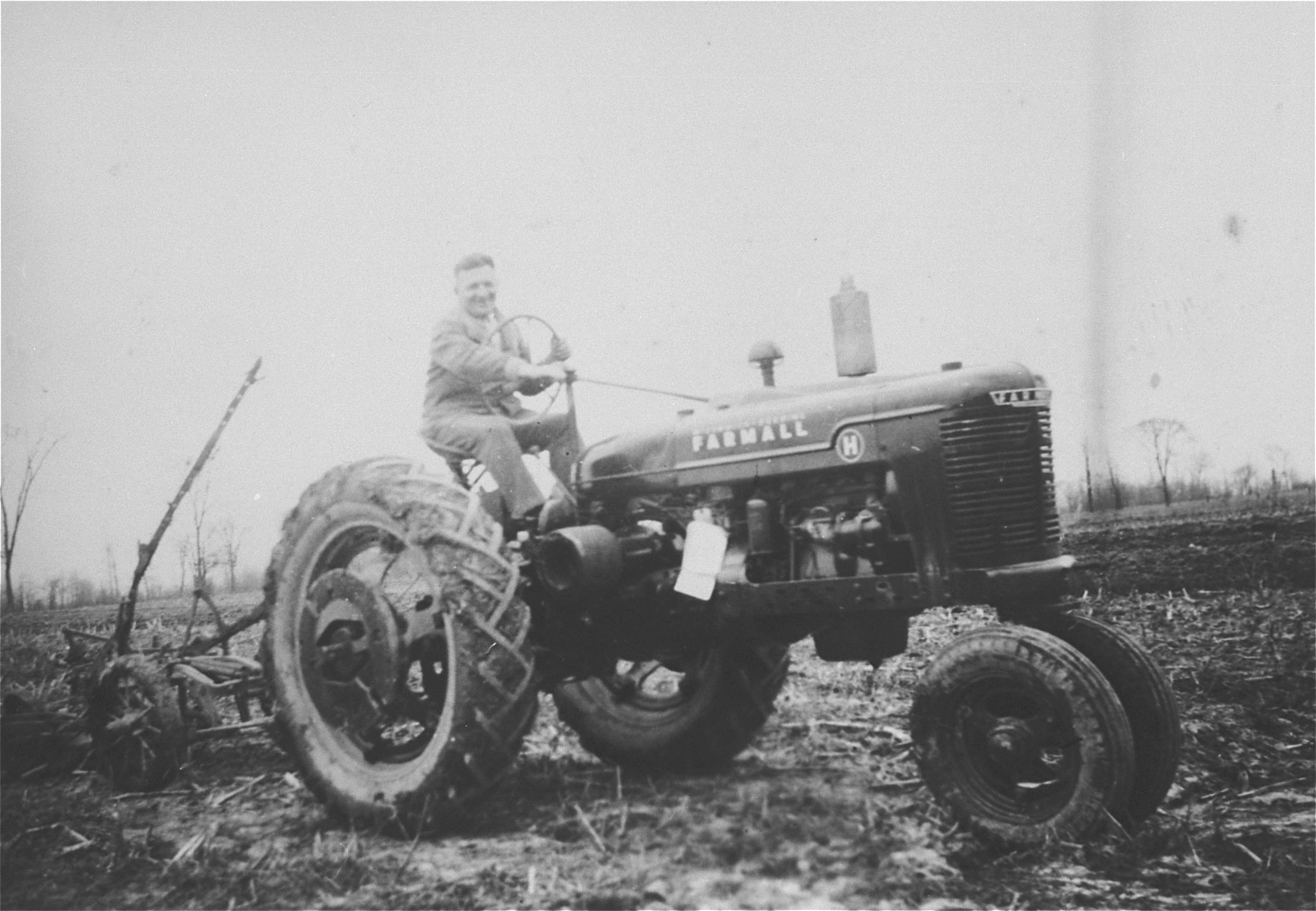 Slovak-Jewish refugee Nandor Muller driving a tractor he bought to work his farm in southern Ontario.