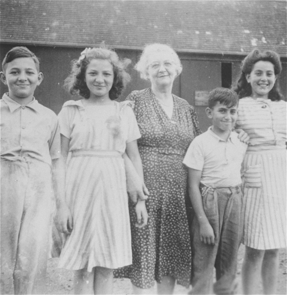 Group portrait of the Muller cousins on their farm in southern Ontario.  Pictured at the left are Henry and Alice Muller, and at the right, Agnes and George Muller.