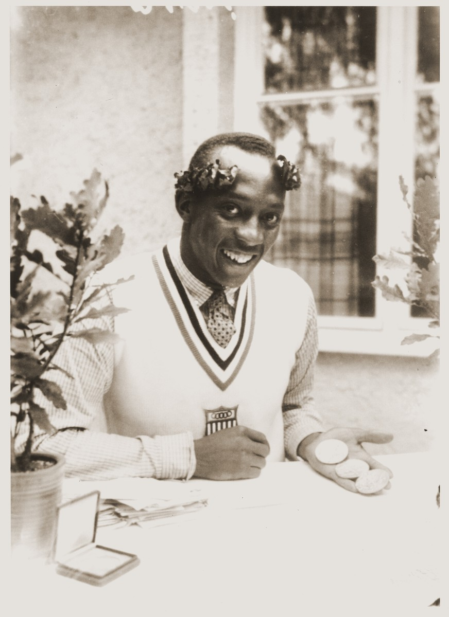 Jesse Owens, posing with his three gold medals, at the 11th Summer Olympic Games. He won gold in the men's 100m and 200m races and the broad jump.