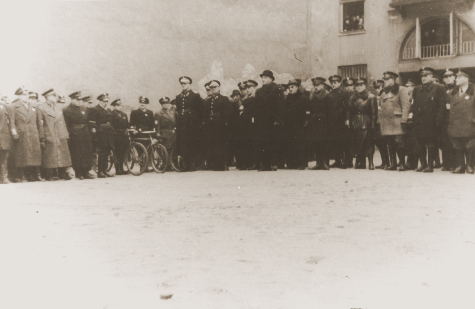 "Adam Czerniakow (center), the Chairman of the Warsaw ghetto Jewish council, poses with visiting Polish police during a ceremony held in honor of Jewish policemen killed in the line of duty.    The ceremony was held in the inner courtyard of the Jewish Council headquarters on Grzybowska Street and was attended by Aleksander Resczynski, the commander of the Warsaw Polish police (standing center-left, at the end of the first row, to Czerniakow's right).  This photograph was included in the ""Oneg Shabbat"" clandestine archive, assembled by Emanuel Ringelblum."