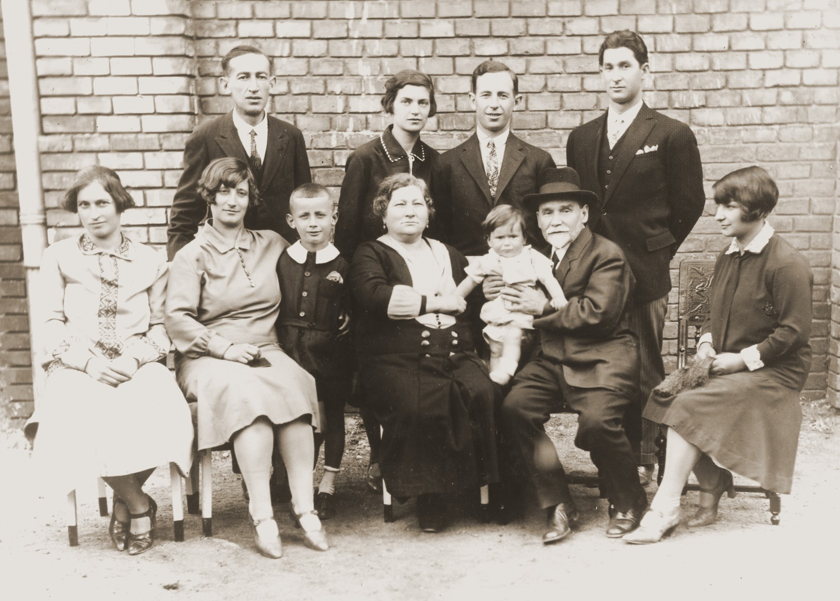 Portrait of the extended Kupfermann family in Budapest.  Pictured in the front row from left to right are Rezinka and Piri Kupfermann, Gyury Friedman, grandmother Kupfermann, Aurel Kupfermann, Osias Kupferman, and Boriska Kupfermann.  Standing from left to right are: Arpad Friedman, Blanka and Beno Kupfermann, and Andres Kupfermann.  Osias Kupferman was the cantor of a synagogue in Buda.  Arpad and Piri (Kupfermann) Friedman and their son Gyury later emigrated to Uruguay.  Andres Kupferman was an opera singer, whose stage name was Andor Koves.  He was also an athlete who had won medals at the 1928 Olympics.  He also emigrated to Uruguay.
