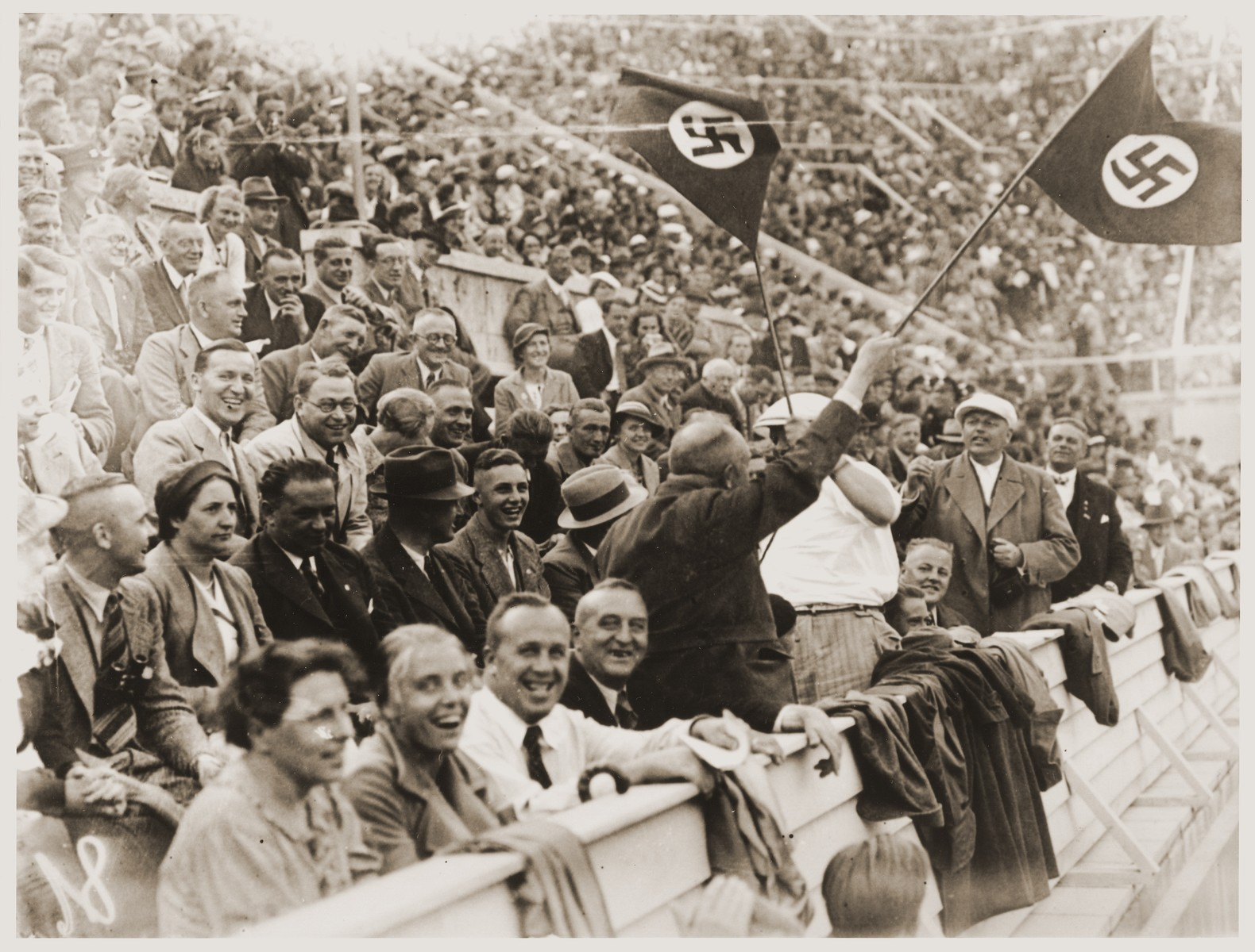 Spectators cheer on the Germans at the 11th Summer Olympic Games.