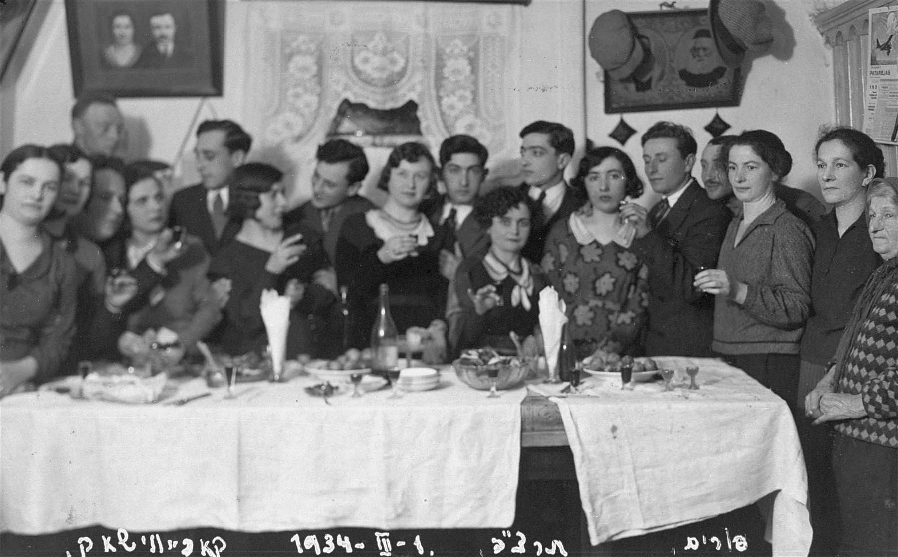 A family gathering on the Jewish holiday of Purim. Pictured seventh from the right (behind the two women) is Eliezer Kaplan, the donor's father.