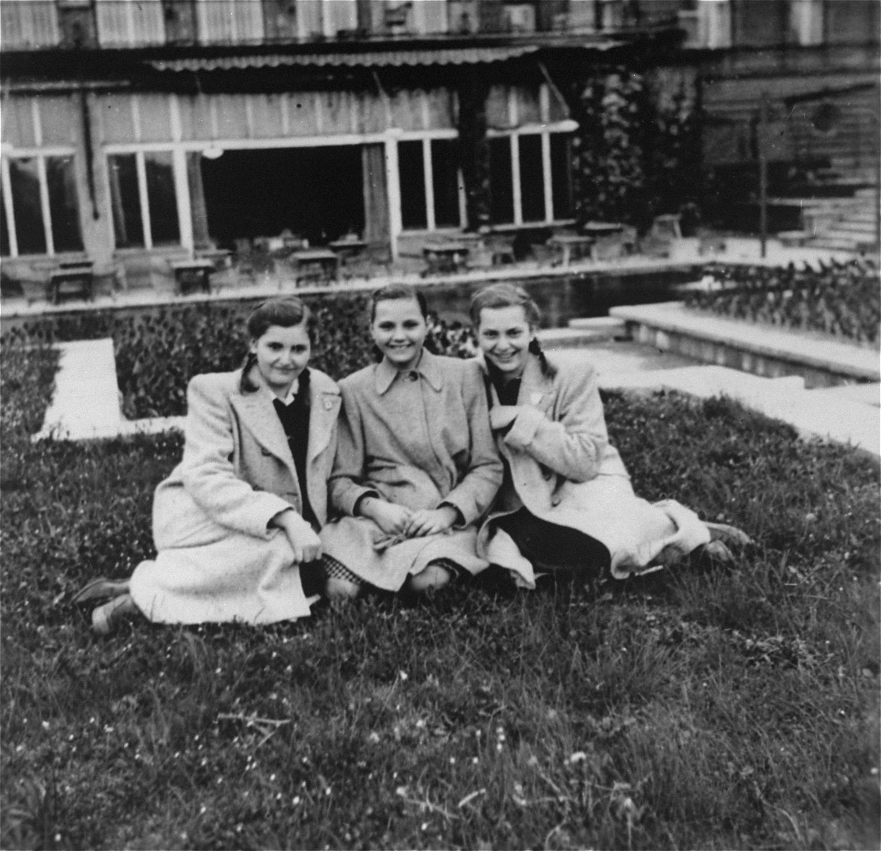Dorottya (Dolly) Dezsoefi, left, with twin sister, Ida Marianne (Mari), right, and a friend, sit outside while in hiding at the Hotel Lukacs.