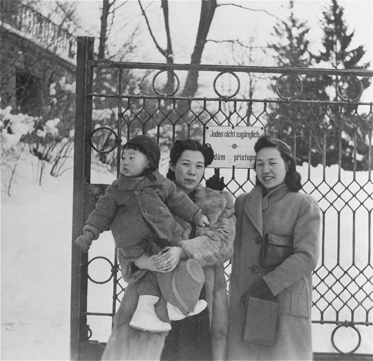 "Yukiko Sugihara (holding Hiroki) and her sister Setsuko Kikuchi pose in front of a park gate in Prague.  The posted sign reads ""Jews not allowed"" in German.  However the lower line in Czech reads ""Jews Allowed"". Someone as covered or scratched out the no in the Czech line.   The Sugihara family moved to Prague in mid-September 1940 after Chiune was declared 'Persona Non Grata' in Berlin.  They remained in Prague until the closing of the consulate on 15 February 1941."
