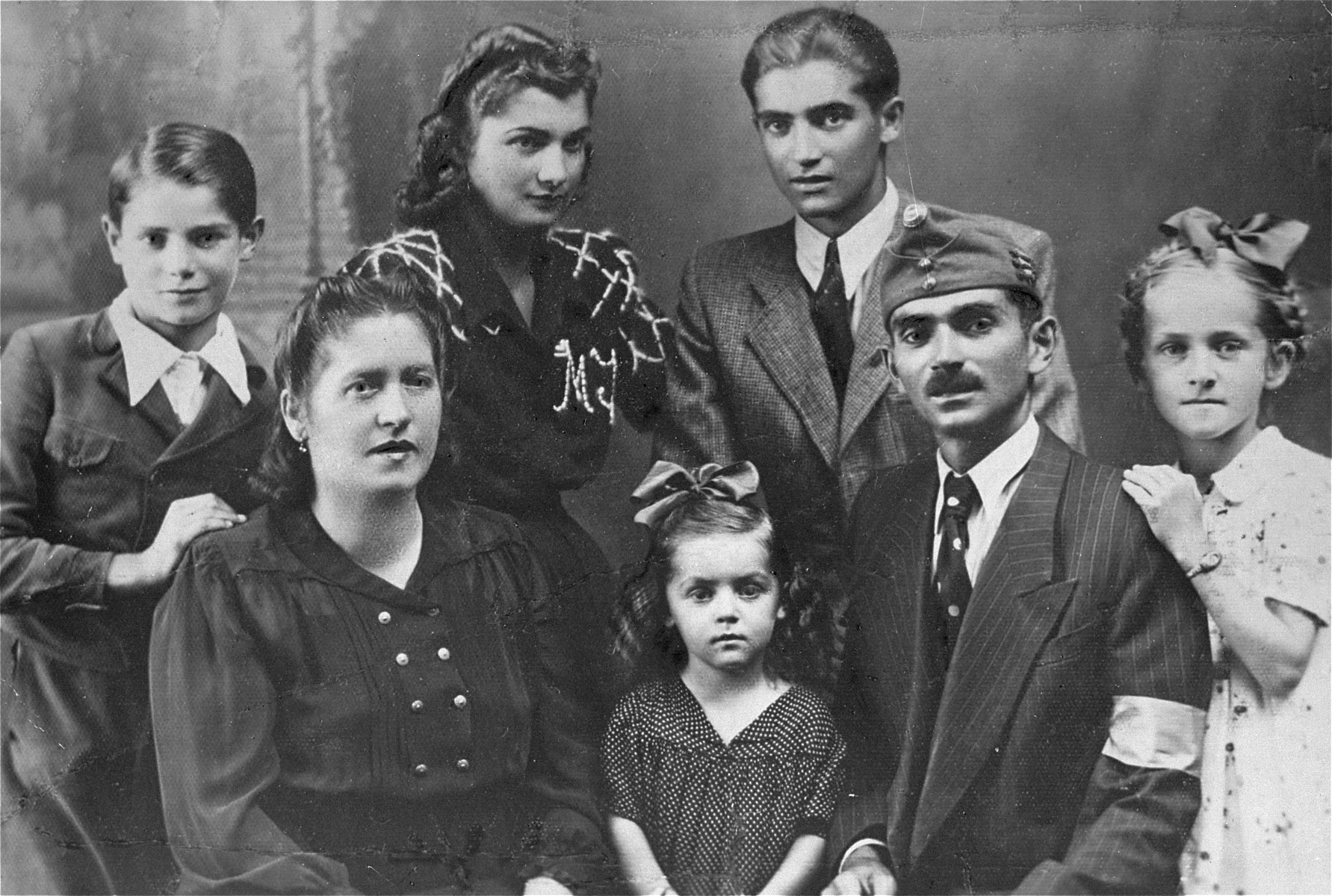 Studio portrait of the Markovits family in Cluj.    Pictured in the front row (left to right) are: Irena, Eva, David, Ilonka; in the back row (left to right) are: Simon, Jolanda and Andre (the donor).  The photo was taken on the occasion of the visit by David Markovits, who had been allowed a one-day leave from his Hungarian labor brigade unit.  Immediately upon his return to the labor brigade, he was deported to Dachau.  David was liberated in Dachau, but died a short time after, on June 20, 1945.  The donor, Andre Markovits, who was liberated from Buchenwald, returned to Cluj after the war and retrieved this photo from the photographic studio in which it was taken in 1943.  Andre was the sole survivor of his family, who were all deported from the Cluj ghetto to Auschwitz in April, 1944.