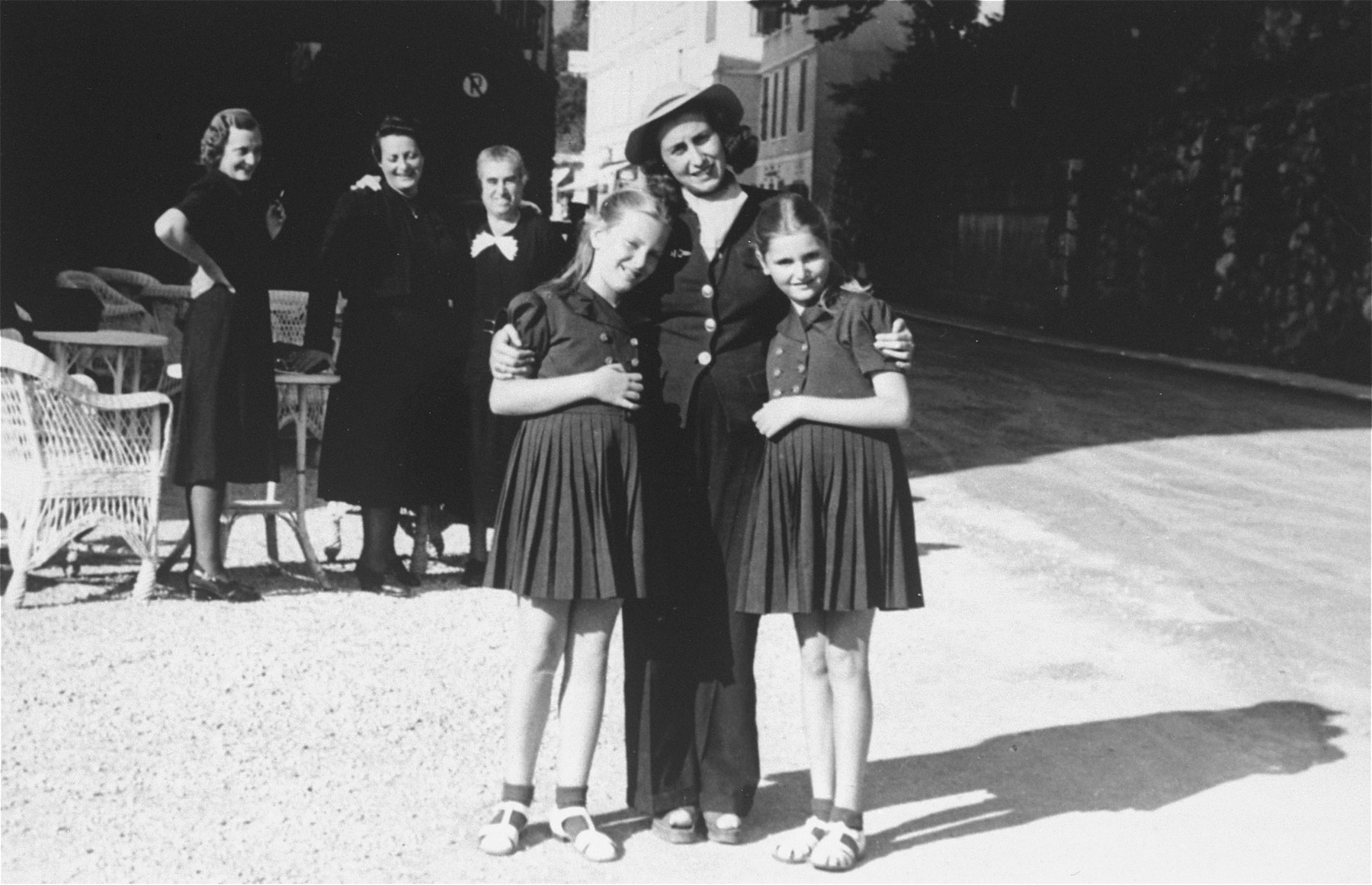 Dolly (left) and Mari Dezsoefi pose with their cousin, Dorothea (Babi) Halberg.    In the background are Johanna Selinger, the twins' mother, standing far left, her sister, Elizabeth Tieberger, center, and family friend, Mrs. Diamant.