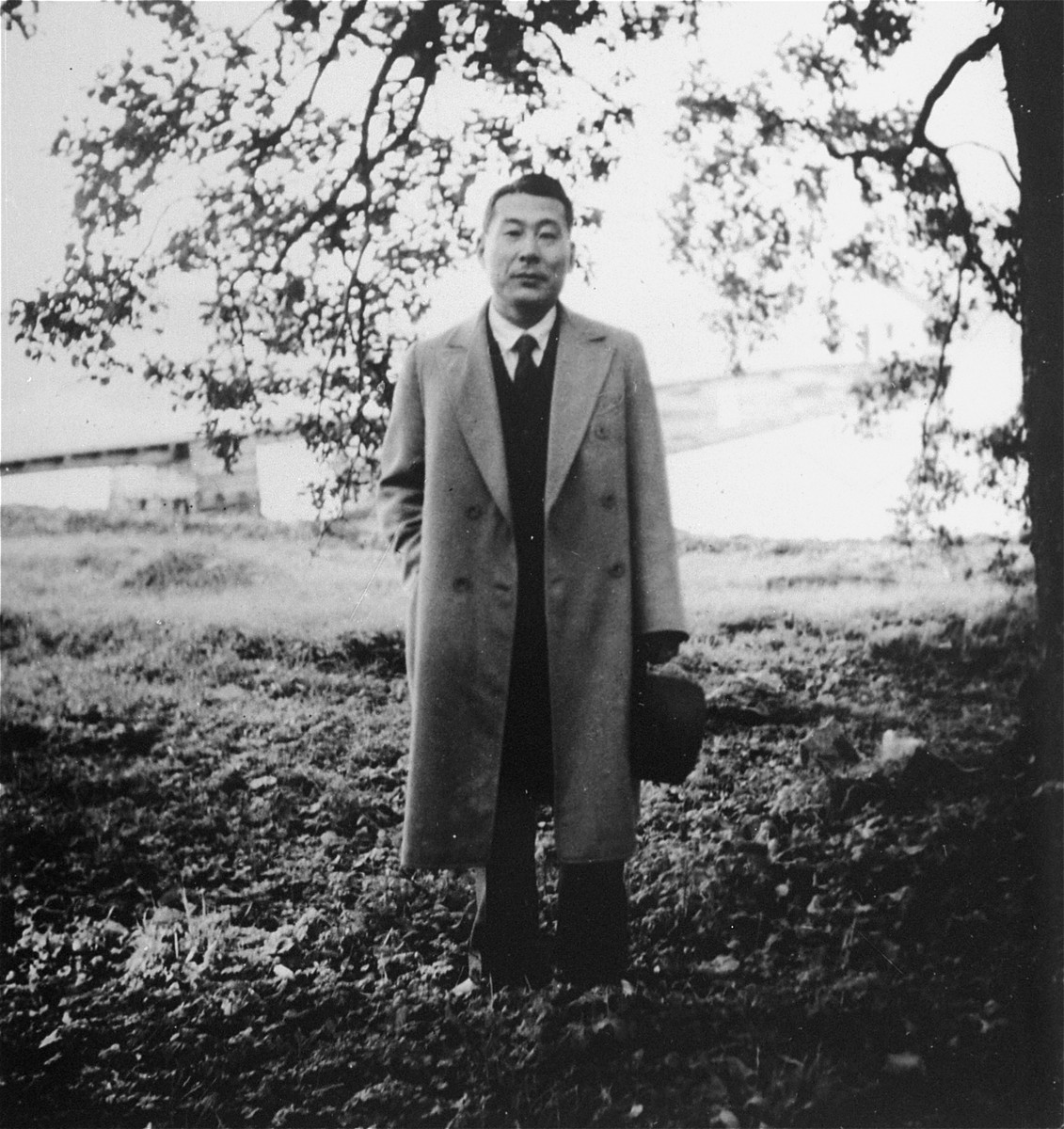 Chiune Sugihara poses outside beneath a tree in Kaunas.