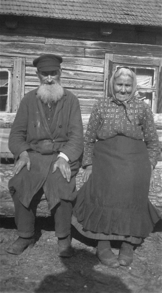 Portrait of an elderly Jewish couple sitting on a log in front of their home in a Lithuanian village. Pictured are the donor's great aunt and uncle.