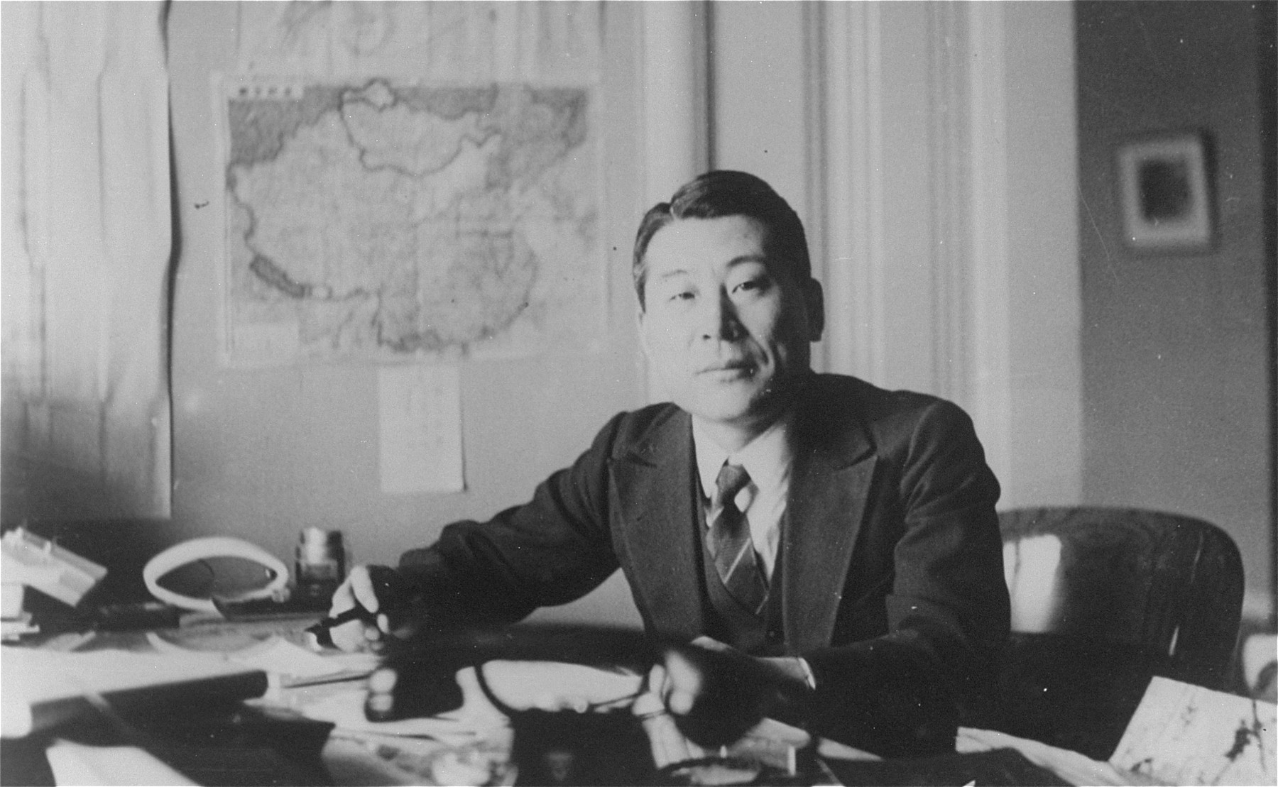 Chiune Sugihara sits at a desk in his office.