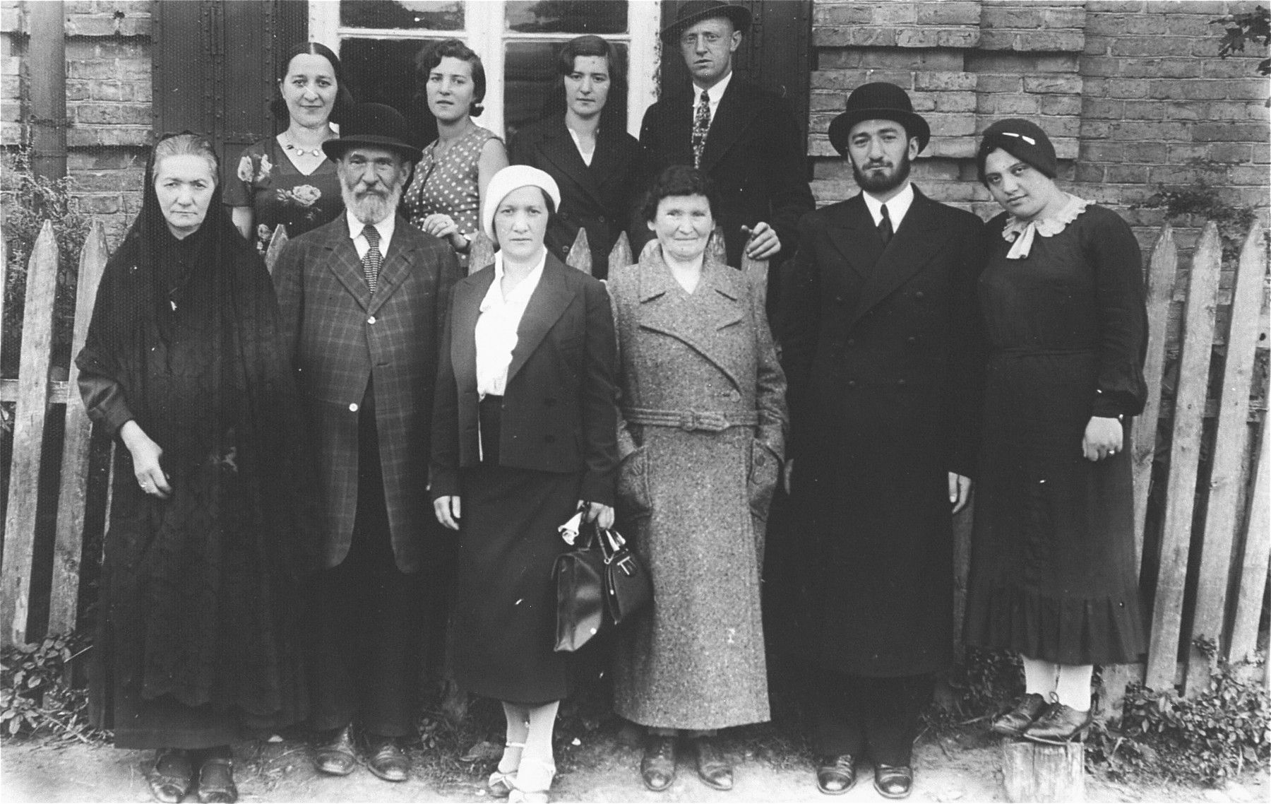 Group portrait of a religious Jewish family in front of their home in Kron?, Lithuania.
