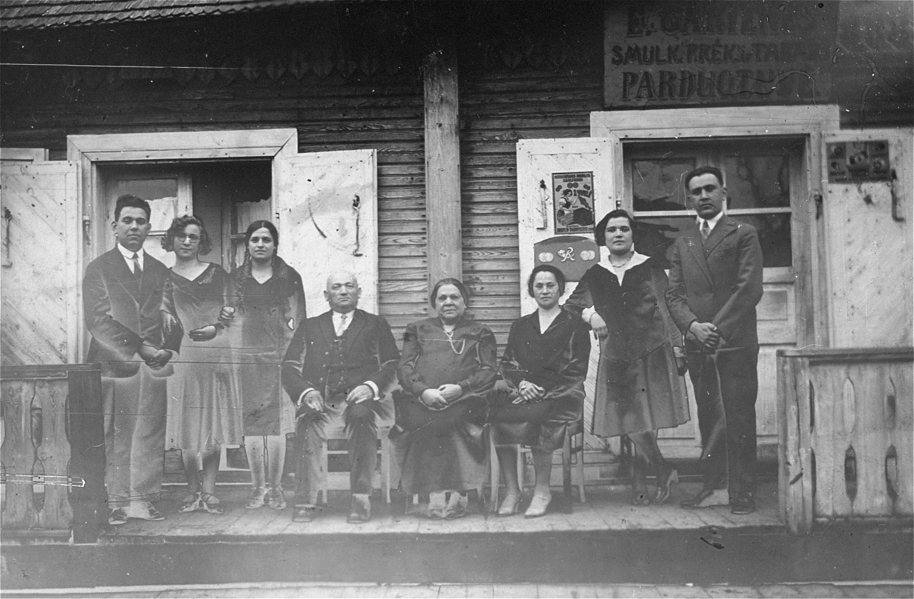 Group portrait of the Gar family in front of the grandmother's home in Kron, Lithuania.  Pictured from left to right are: Joseph Gar, unknown, unknown;  David Gar; Esther Gar; unknown, Chaya Gar; Jacob Gar.
