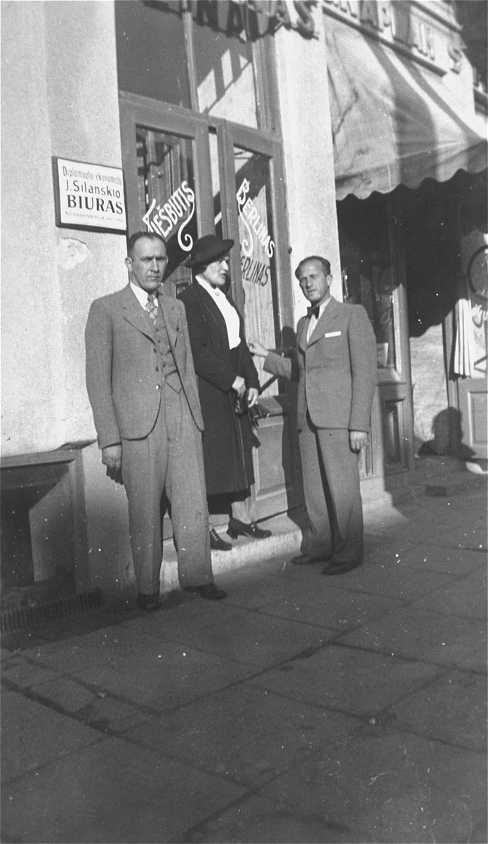 Chaya Gar stands in front of a Jewish-owned shop in Kovno with her brother Jacob and a friend, during her return visit to Lithuania in the summer of 1938.
