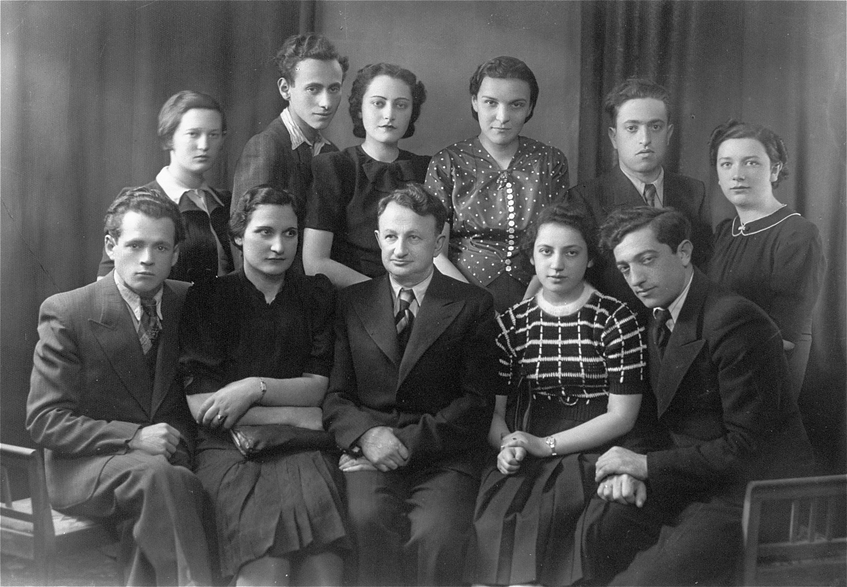 Group portrait of young Jewish men and women in Lithuania. Pictured at the far right in the front row is the donor's father, Eliezer Kaplan.