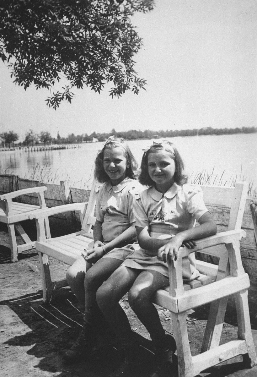 The Dezsoefi twins, (Ida Marianne (Mari) and Dorottya (Dolly), sit on a bench during a resort vacation.