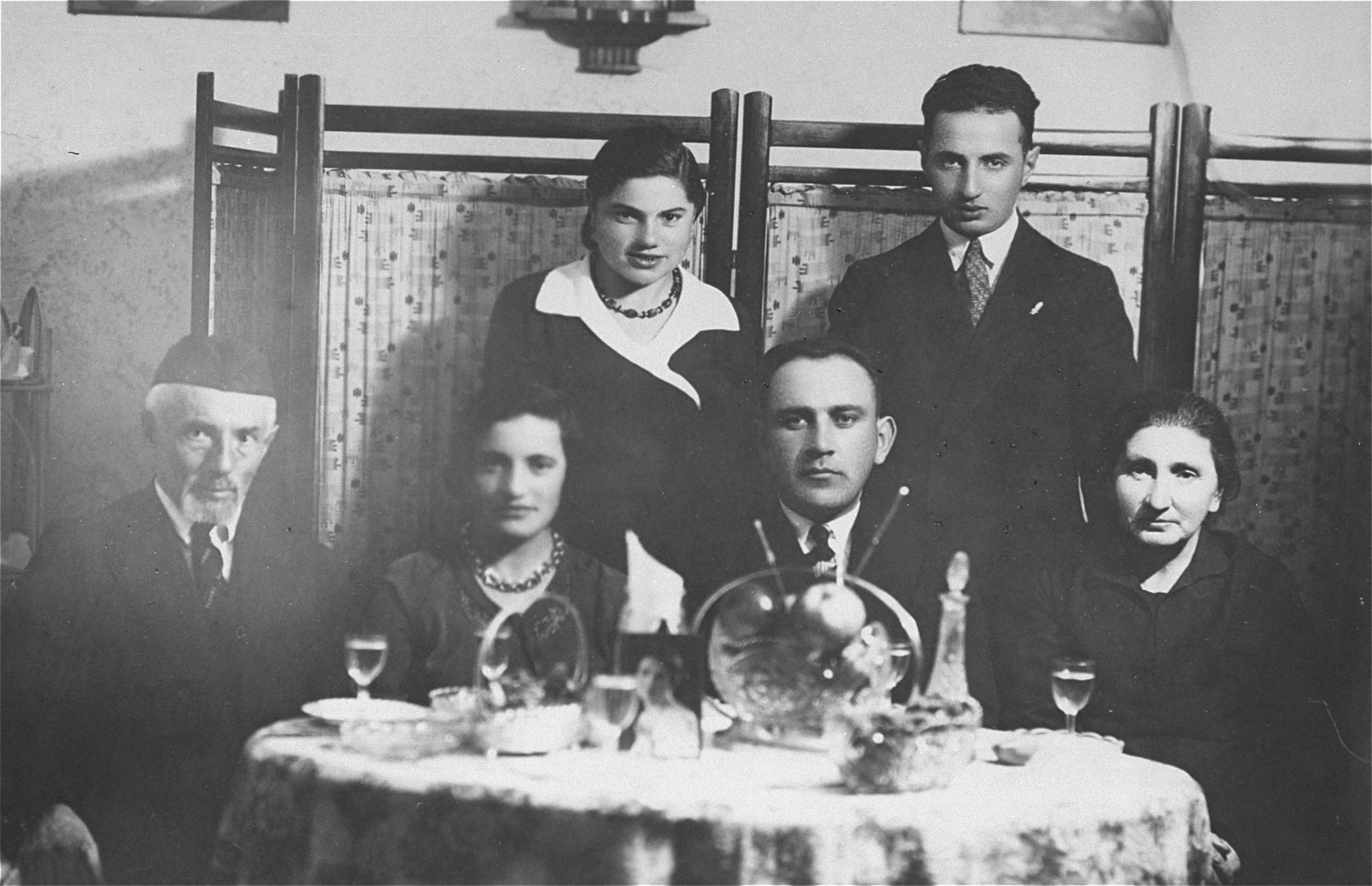 Group portrait of a lithuanian-Jewish family seated around a dinner table.  Pictured are the donor's uncle and aunt, Jacob and Baila Gar (standing) with Baila's parents, brother and sister.