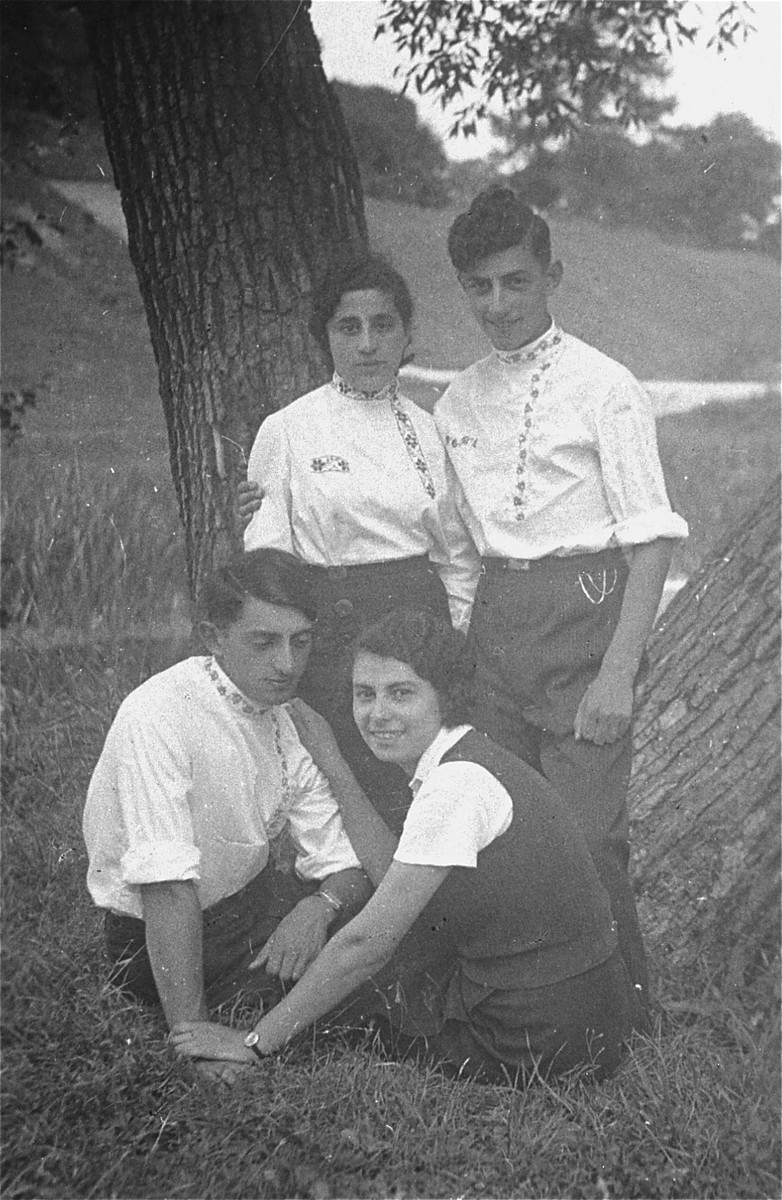 Two young couples wearing embroidered blouses (Jewish folk-dancing costumes) pose in a park. Pictured are the donor's uncles, Shmuel (top right) and Moshe (bottom left) Kaplan, with their girlfriends.
