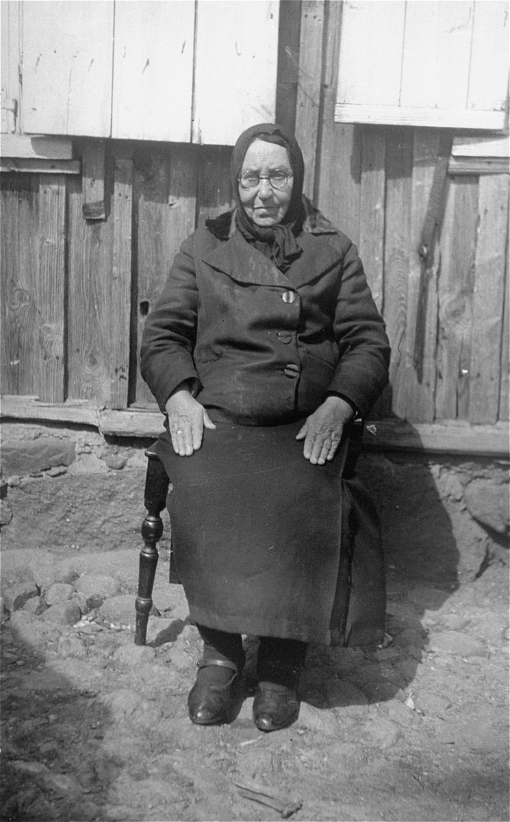 Portrait of an elderly woman from the Olchwanger family sitting in front of her home.