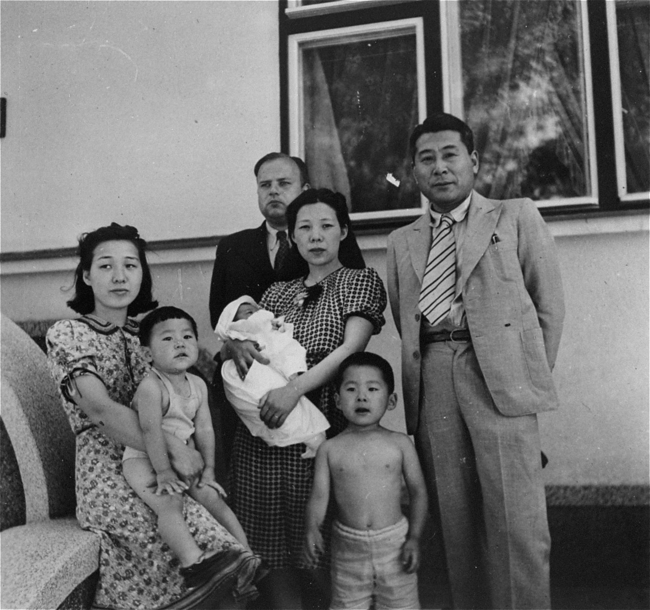 The Sugihara family poses in front of the Japanese consulate in Kaunas.    Yukiko Sugihara is carrying her newborn son, Haruki.  Behind them is the window from which the family watched Jewish refugees from Poland gather to wait for Japanese transit visas.