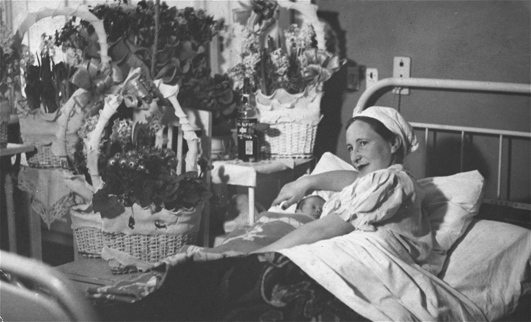 Portrait of Gita Salat Wisgardisky in a hospital in Kovno with her newborn daughter, Henia.