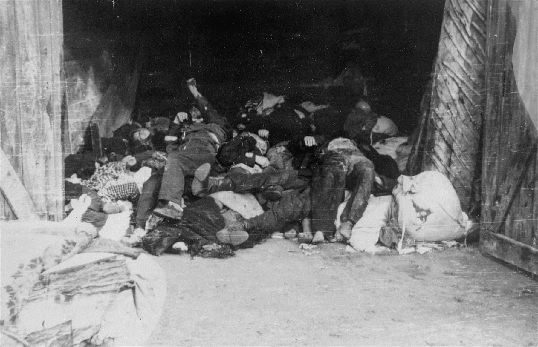 The corpses of Jews are piled up in a barn in the Deblin Irena ghetto.  The corpses of those who were murdered in the ghetto during the expulsion Aktion to Sobibor were transported by cart to the Jewish cemetery in Bobrowniki.  [Source: Yad Vashem research notes.]