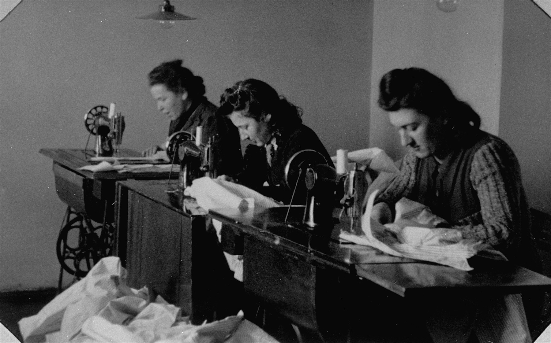 Jewish women work at sewing machines in a workshop in the Bochnia ghetto.