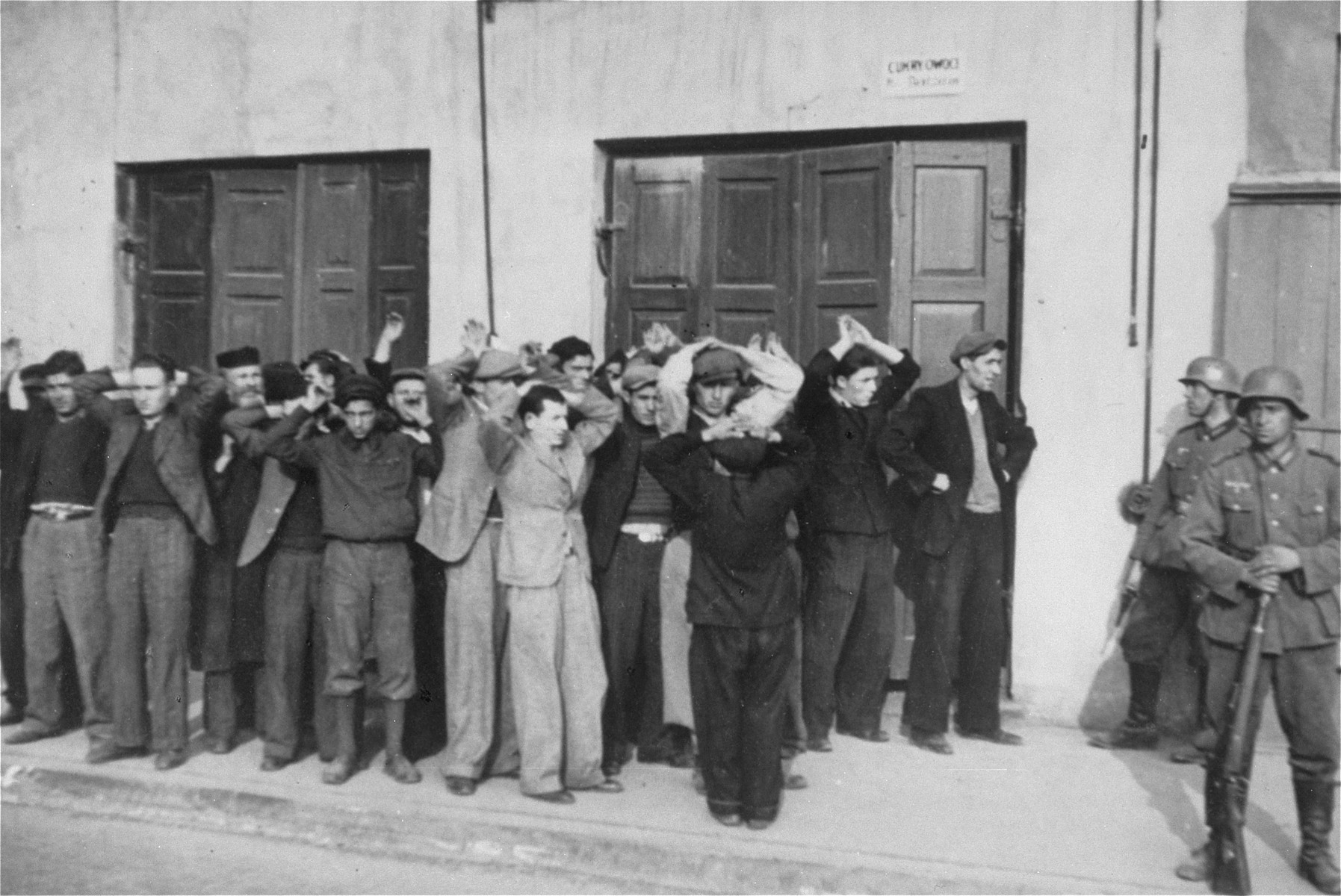 German soldiers round-up a group of Jewish men on a street in Czestochowa.
