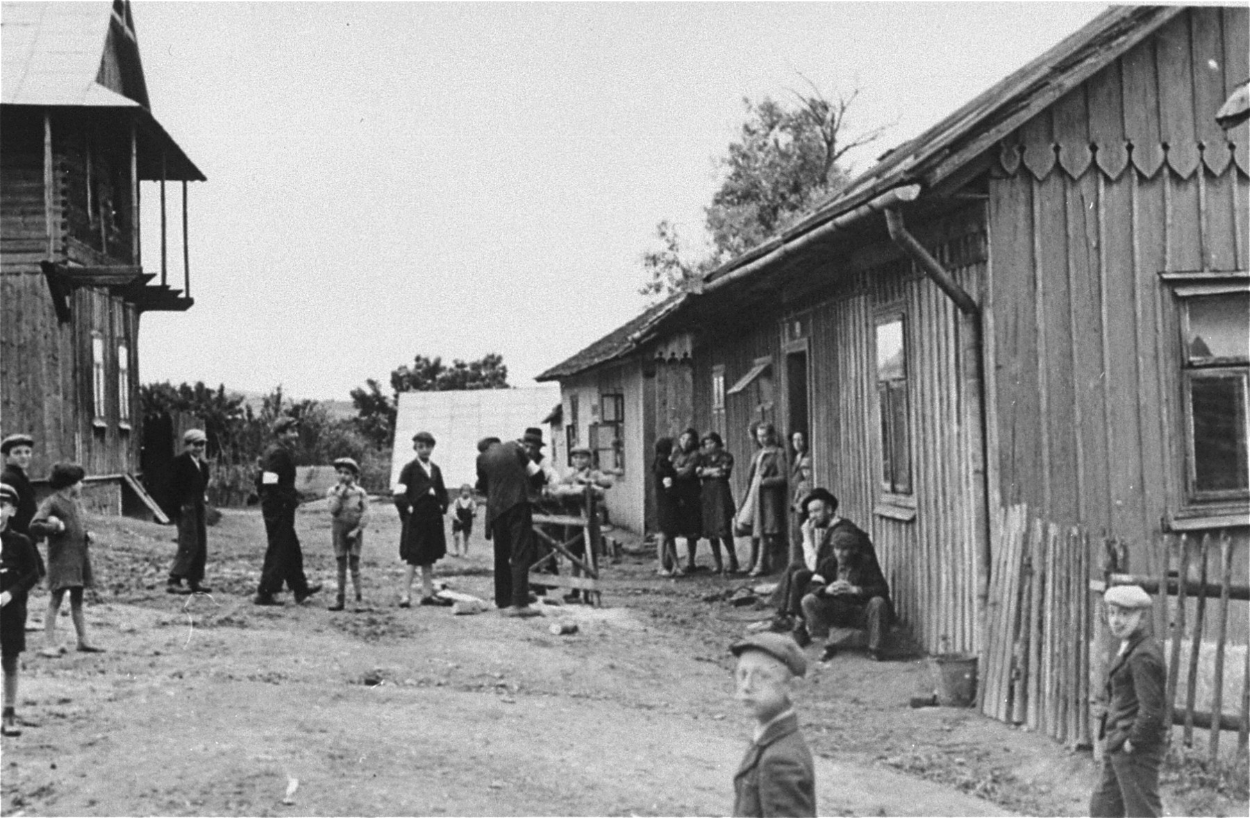 Jews are gathered outside on an unpaved street between rows of wooden houses in the Frysztak ghetto.