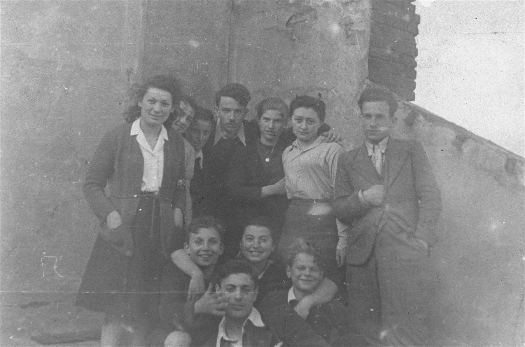 Group portrait of Jewish survivors who are members of a kibbutz hachshara located at 38 Poznanska Street in Warsaw.    Among those pictured are: Uta Wargon Grajek (standing at the left) and Israel Szklar (standing in the center).