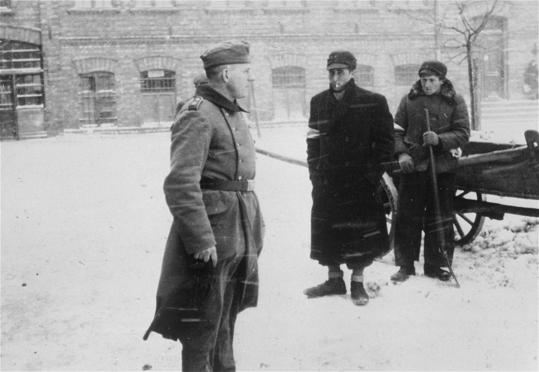 A German soldier stands next to two Jewish men who are clearing snow on a street in Czestochowa.