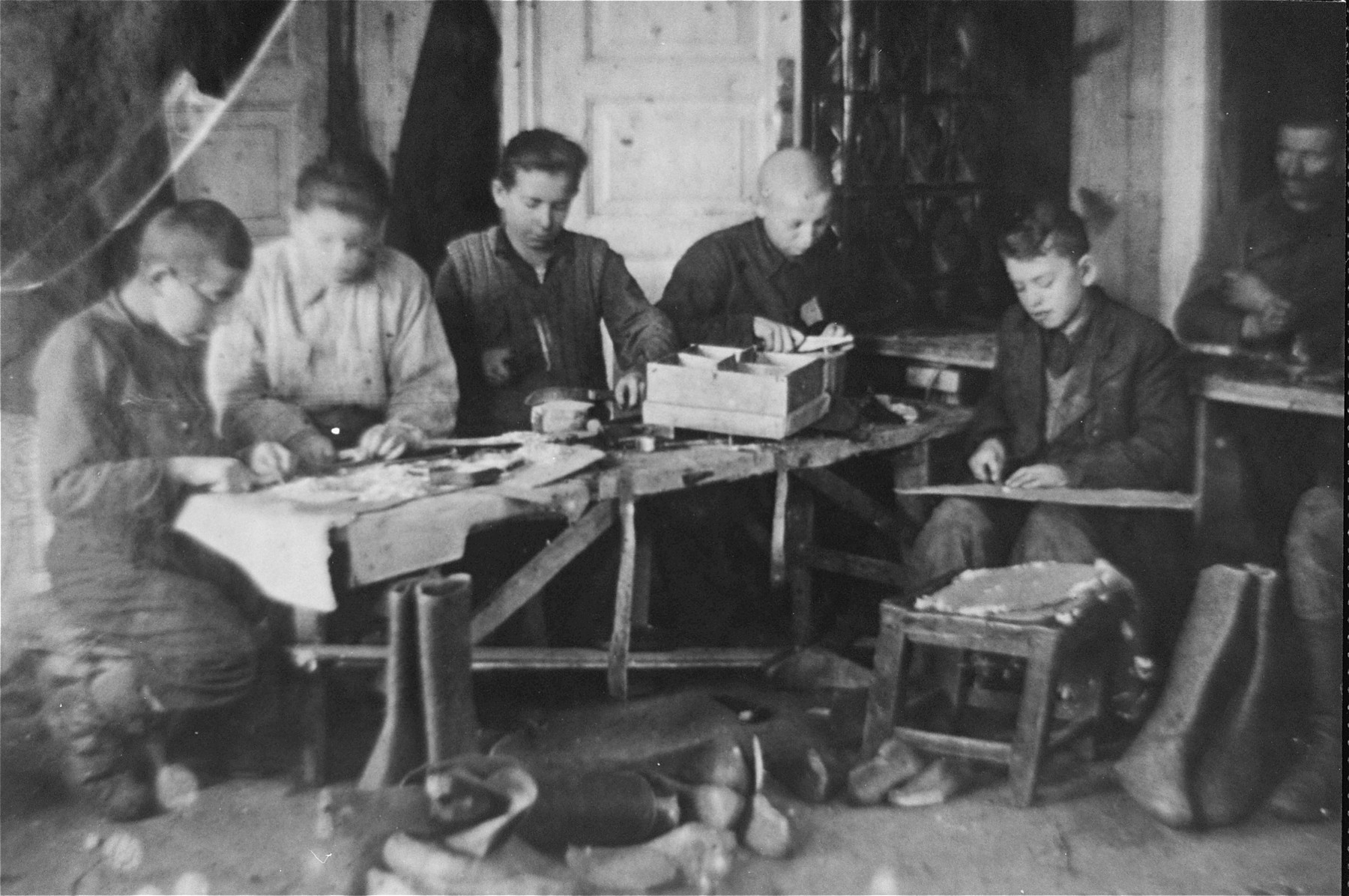 Jewish youth at work in a shoemaking workshop in the Glubokoye ghetto.