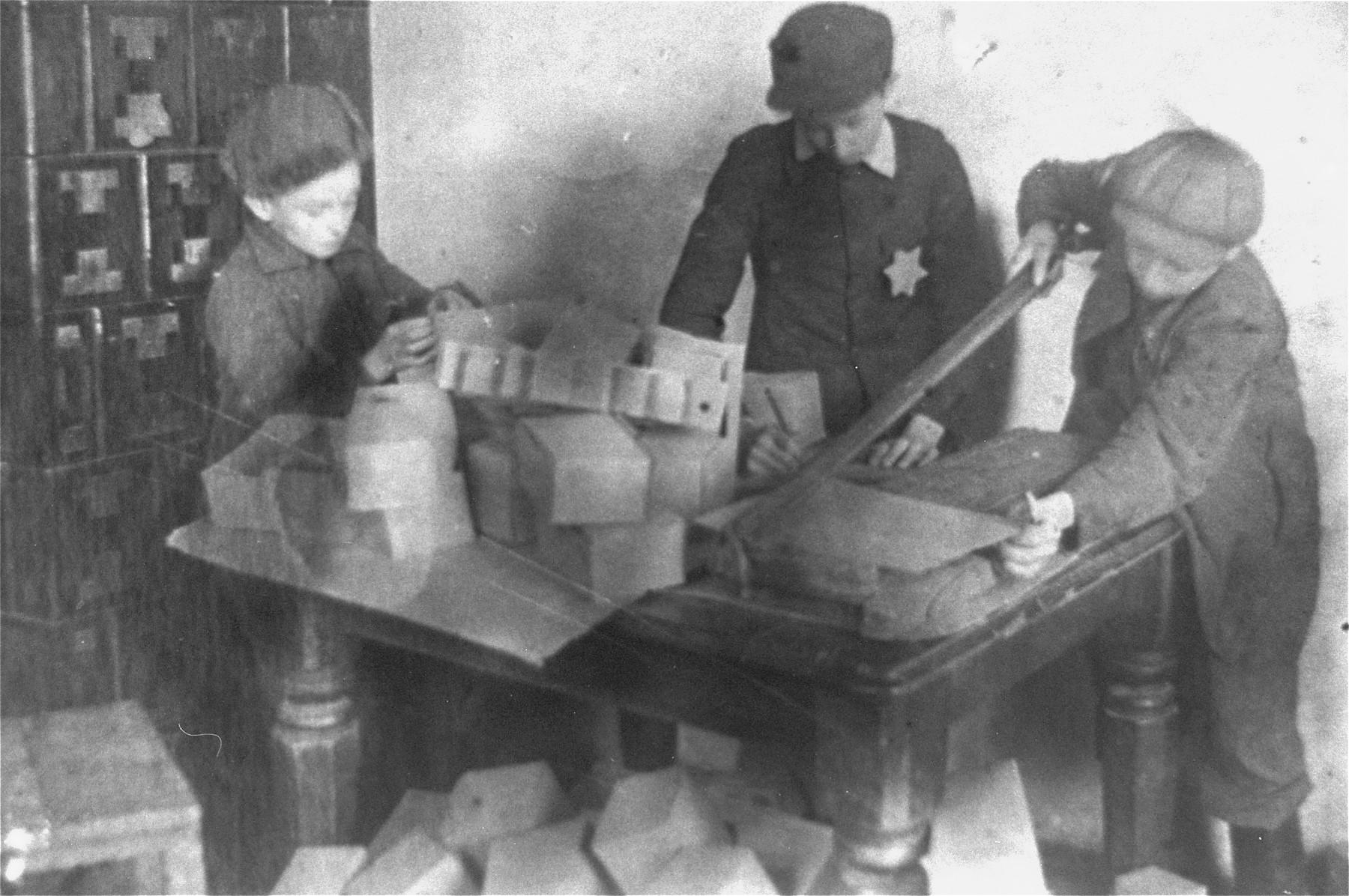 Jewish children making boxes in the Glubokoye ghetto.
