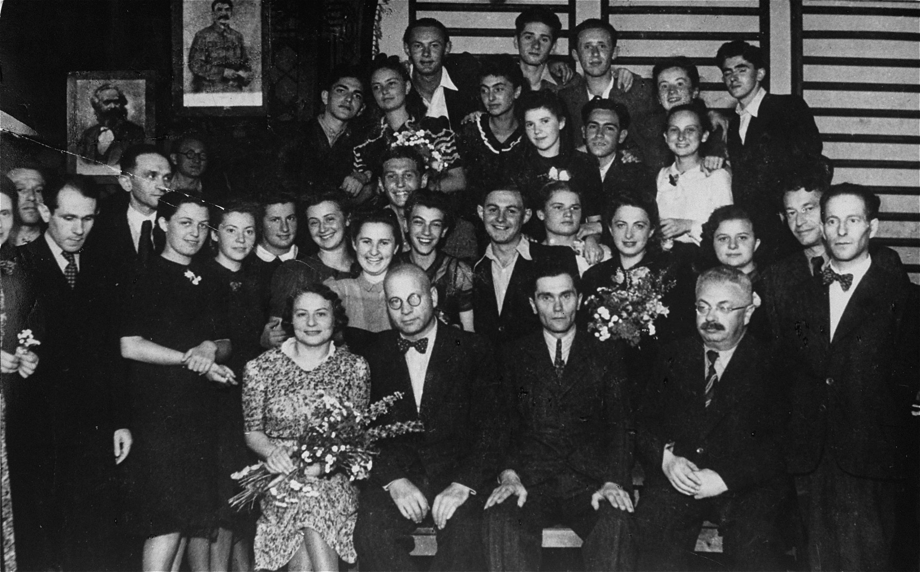 Group portrait of the faculty and graduating class of the Jewish private high school in Drohobycz.  Among those pictured are Bruno Schulz, the Polish author and painter (standing at the left looking down).  Also pictured seated (far left) Mrs. Alter and Jakob Blatt, the principal (far right).  Standing second row, left to right are Bruno Schultz, Mr. Ornstein, unknown, Helena Beck, unknown, unknown, unknown, Tusia Schenkelbach, Ozia Stranzer, Olga Salata, Mrs. Rosberger (nee Harz), Sima Iwaszczenko, Nemlich, Adolph Hirschberg.  Third row: Stempler (?), Ida Hennenfeld, unknown, Rysia Resnick, unknown, and  Lola Oppenheim.  Top row:  Kaiko Kupferberg,  Imek Weiss, Bloch, unknown and a Jewish refugee from Vienna.  Others pictured are Rudek Lanc, and Fredek Koch.