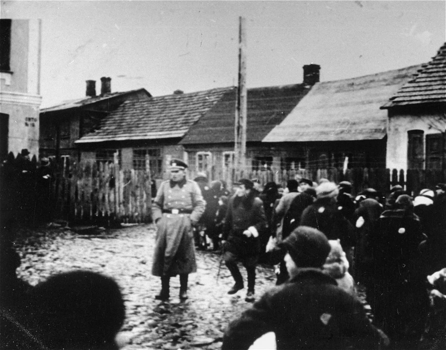 A German police officer stands in a fenced-in yard among a group of Jews, who have been rounded-up in the Ciechanow ghetto.