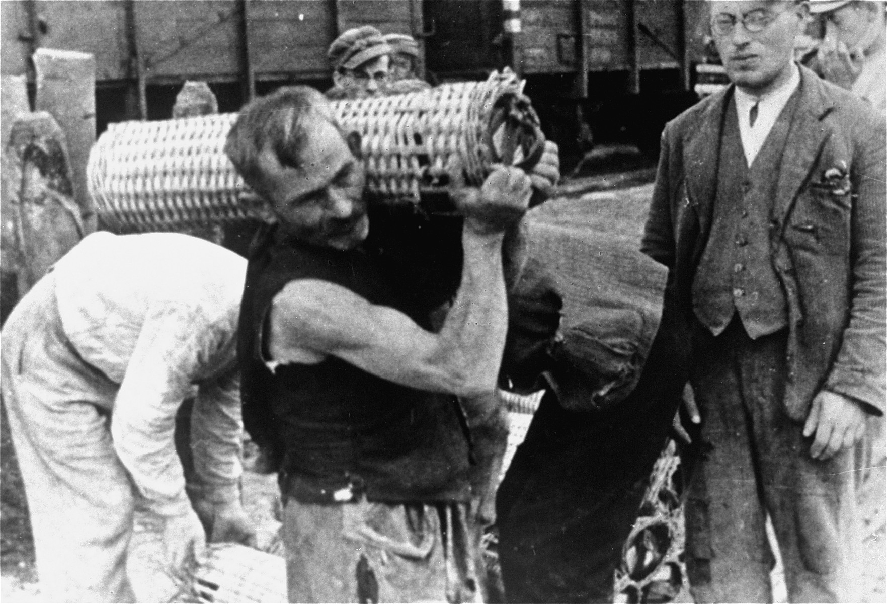 Jewish men are forced to load a German munitions train.