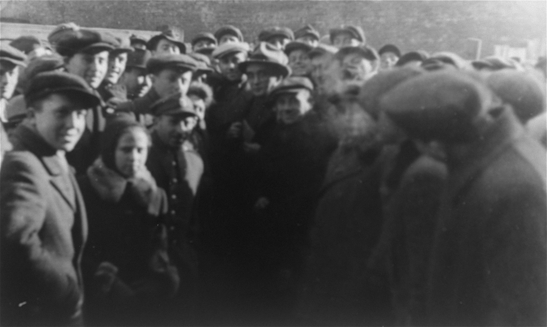 Jacob Pat, a representative of an American Jewish Labor Committee, surrounded by Jewish survivors on the site of the former Warsaw ghetto.